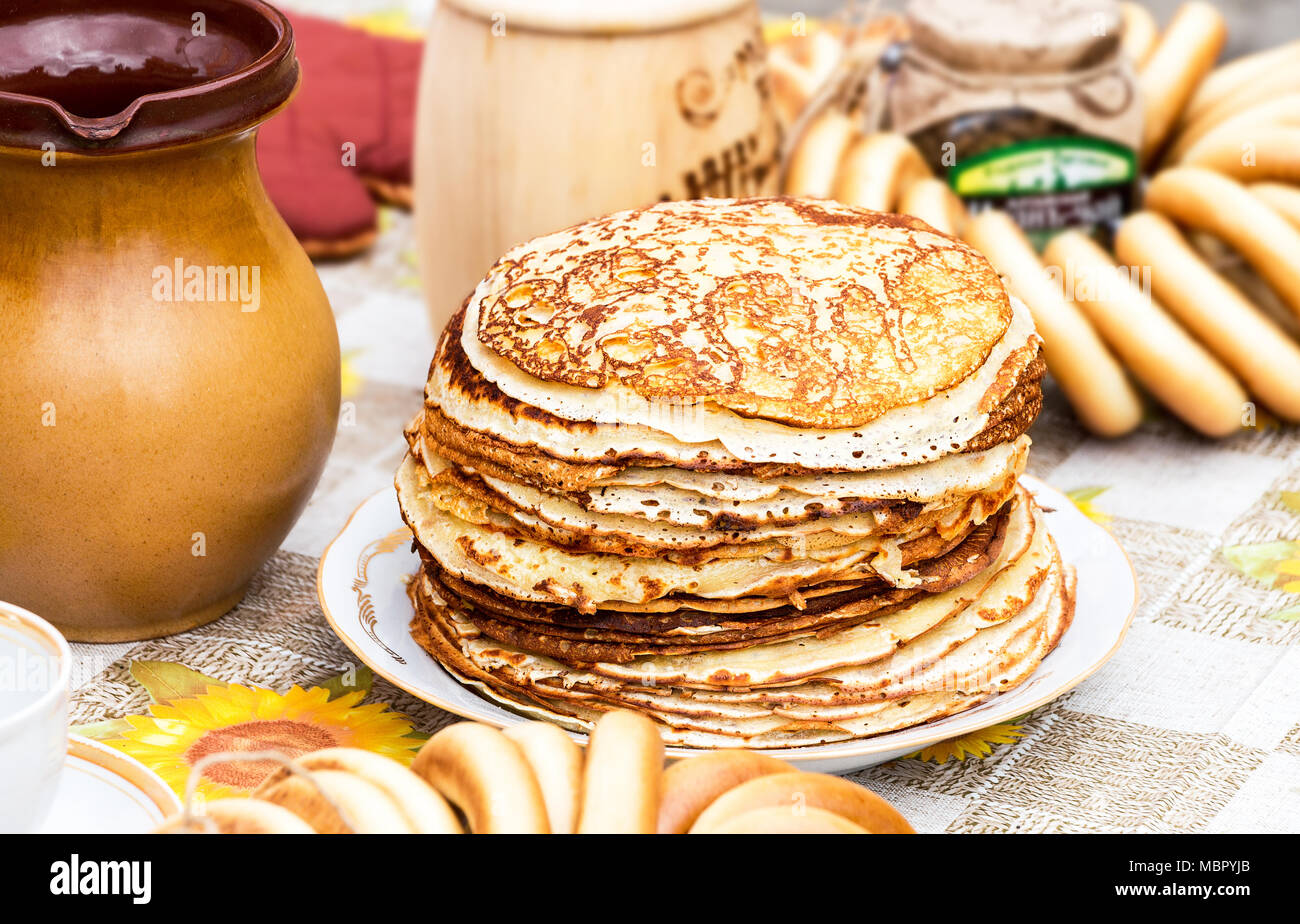 Russian traditional food. Stack of appetizing fried pancakes and bagels on the table during Pancake Week - Stock Image