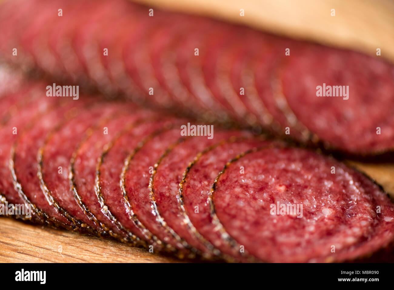 Macro of smoked salami sausage background. Top view, copy space. Sliced salami texture close up - Stock Image