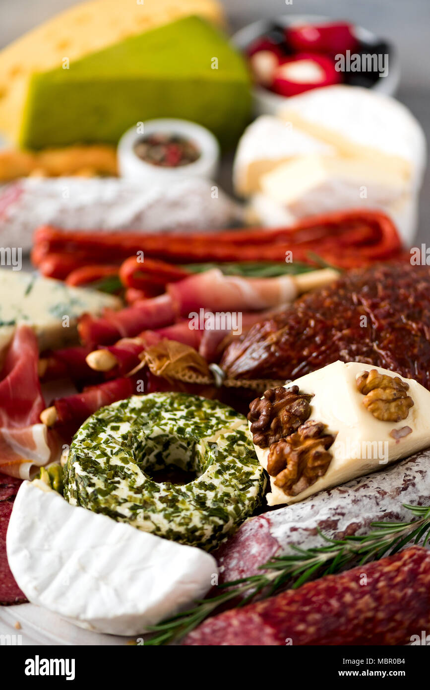 Traditional italian antipasto, cutting board with salami, cold smoked meat, prosciutto, ham, cheeses, olives, capers on grey background. Cheese and meat appetizer. Stock Photo