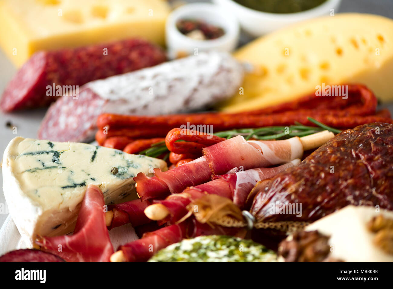 Cold smoked meat plate. Traditional italian antipasto, cutting board with salami, prosciutto, ham, pork chops, olives on grey background. Top view, copy space, flat lay - Stock Image