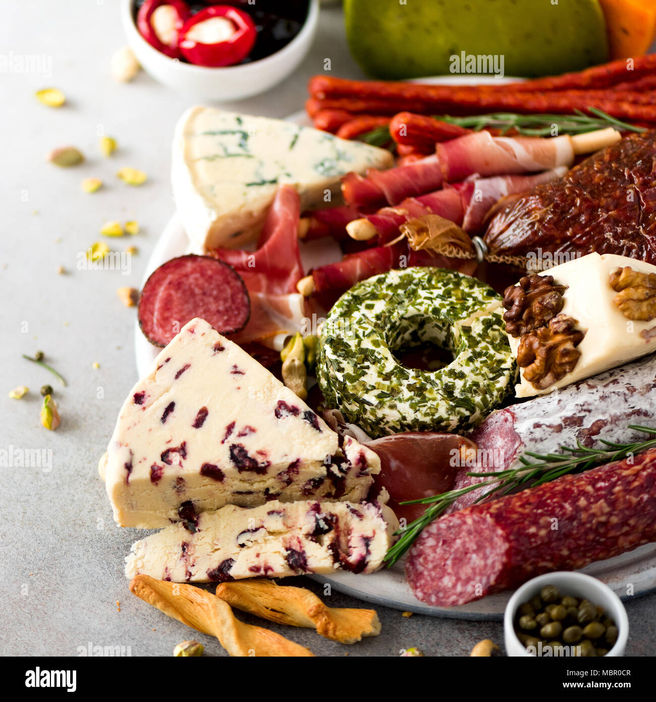 Traditional italian antipasto, cutting board with salami, cold smoked meat, prosciutto, ham, cheeses, olives, capers on grey background. Cheese and meat appetizer. Square crop - Stock Image