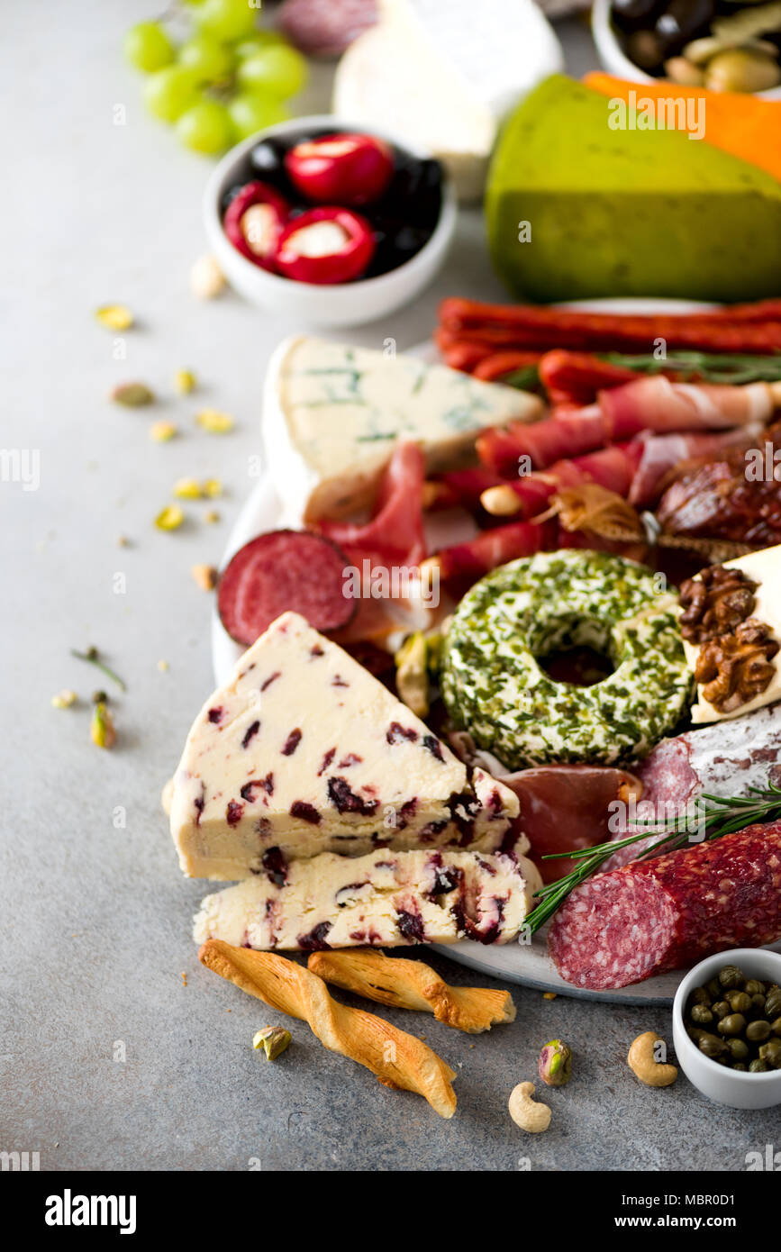 Traditional italian antipasto, cutting board with salami, cold smoked meat, prosciutto, ham, cheeses, olives, capers on grey background. Cheese and meat appetizer. - Stock Image