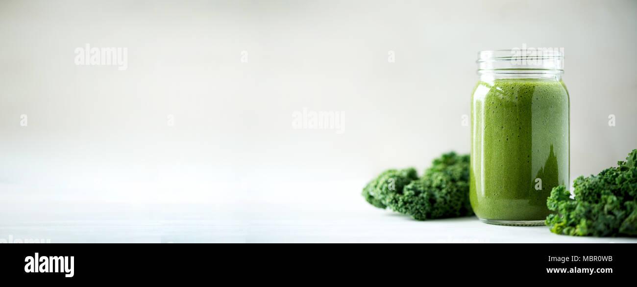 Glass jar mugs with green health smoothie, kale leaves, lime, apple, kiwi, grapes, banana, avocado, lettuce. Copy space, sunlight effect. Raw, vegan, vegetarian, detox, alkaline food concept. Stock Photo