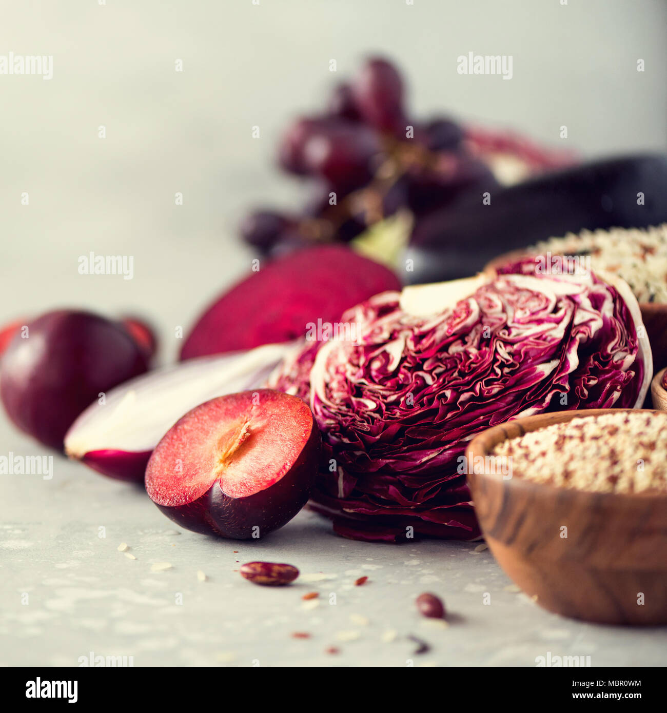 Ingredients for cooking, copy space, top view, flat lay. Purple vegetables, fruits on grey background. Violet eggplant, beets, cauliflower, purple beans, plums, onion, grape, quinoa, rice. - Stock Image
