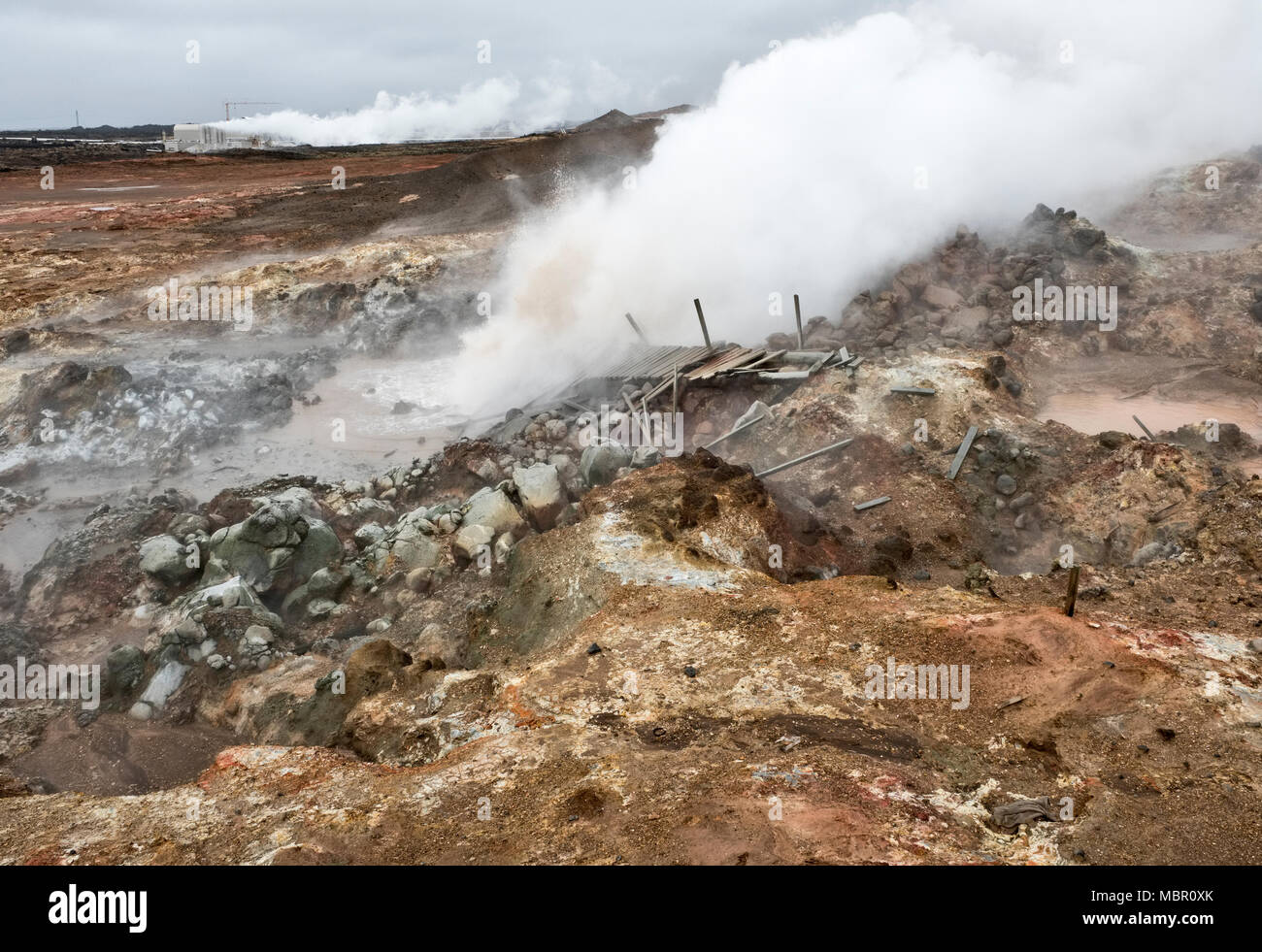 The Reykjanes peninsula, Iceland. A boiling mud pool in the Gunnuhver volcanic area. The Suðurnes geothermal power plant is in the background - Stock Image