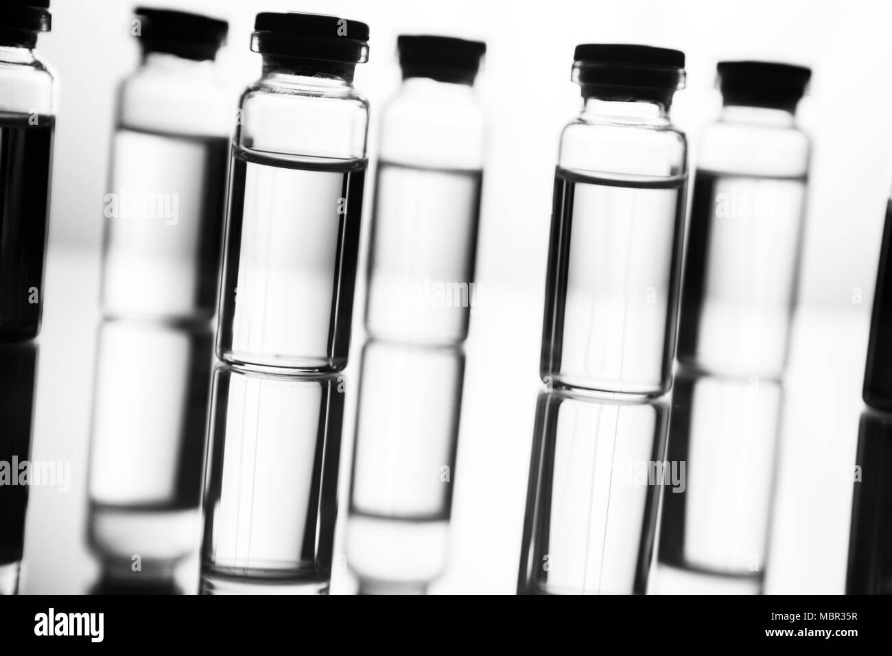 Group of ampoules with a transparent medicine in medical laboratory - Stock Image