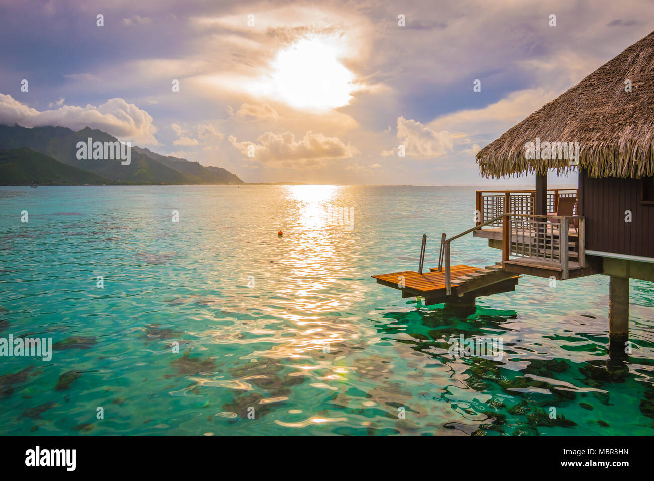 Evening with sunset in Moorea. Overwater bungalow on the side with breathtaking lagoon, French Polynesia - Stock Image