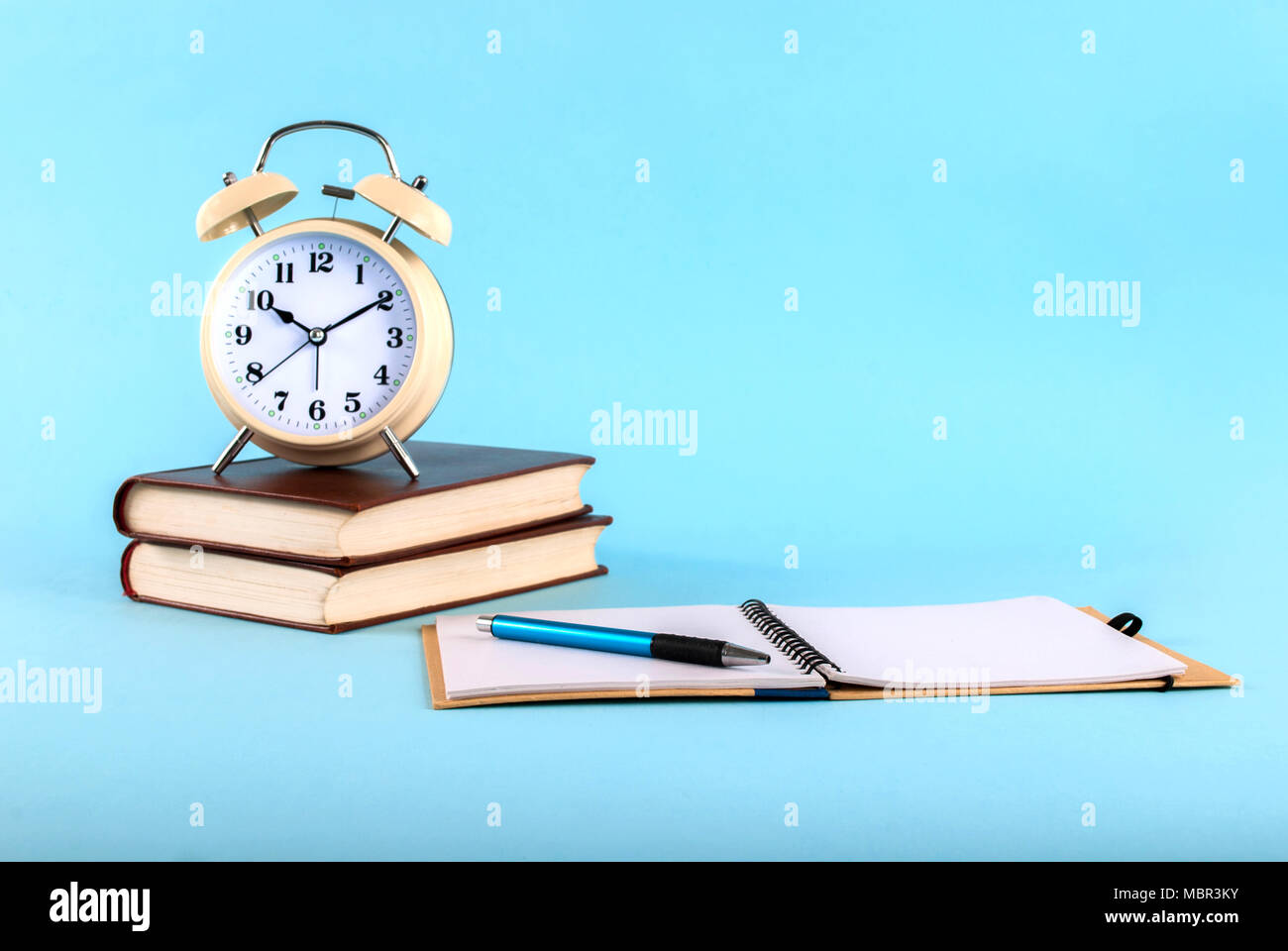 Old clock on books and open notebook isolated by on a blue background Stock Photo