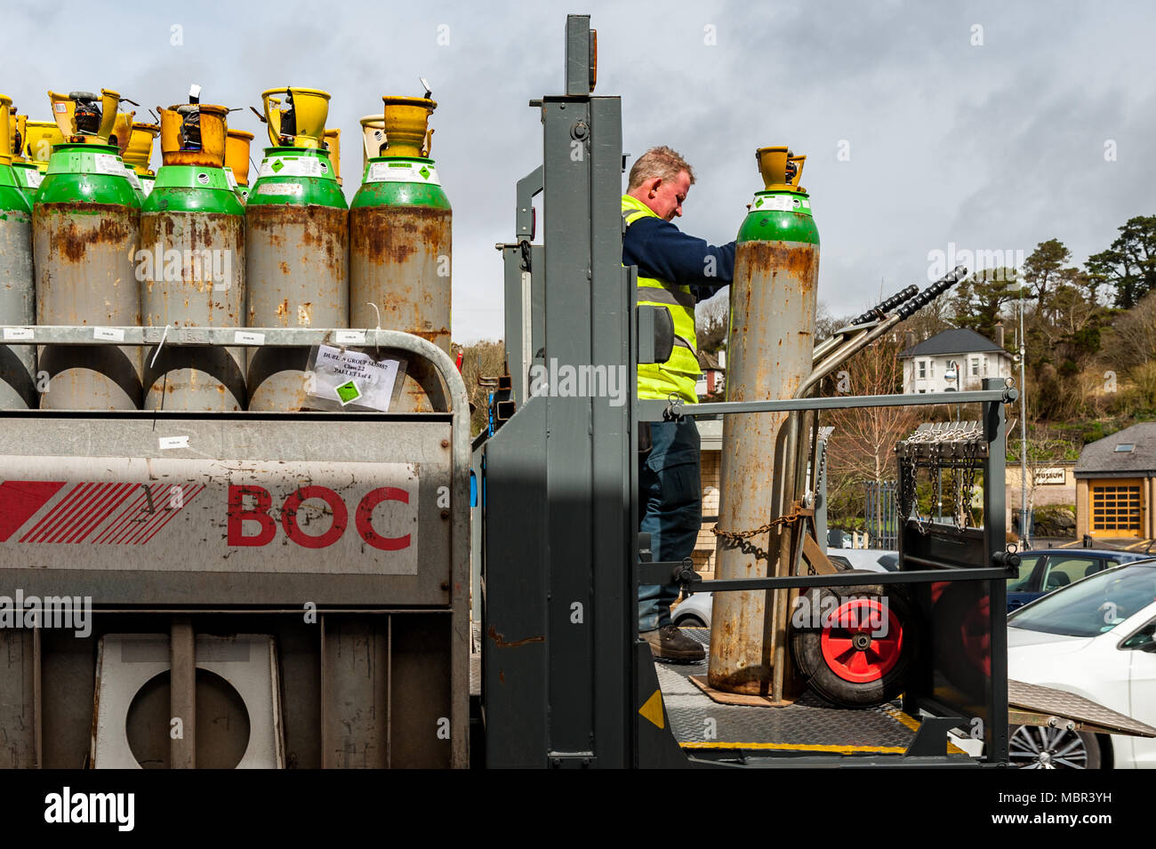 BOC employee delivers a full gas bottle/cylinder to a pub in Bantry Town Square, Bantry, West Cork, Ireland with copy space. - Stock Image