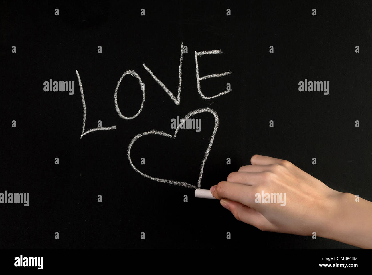 Girl Hand Write Word Love And Drawing Heart On Blackboard With White Chalk