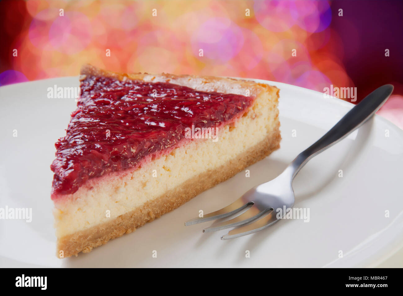 Slice of Raspberry Cheesecake on a white plate; Close up - Stock Image