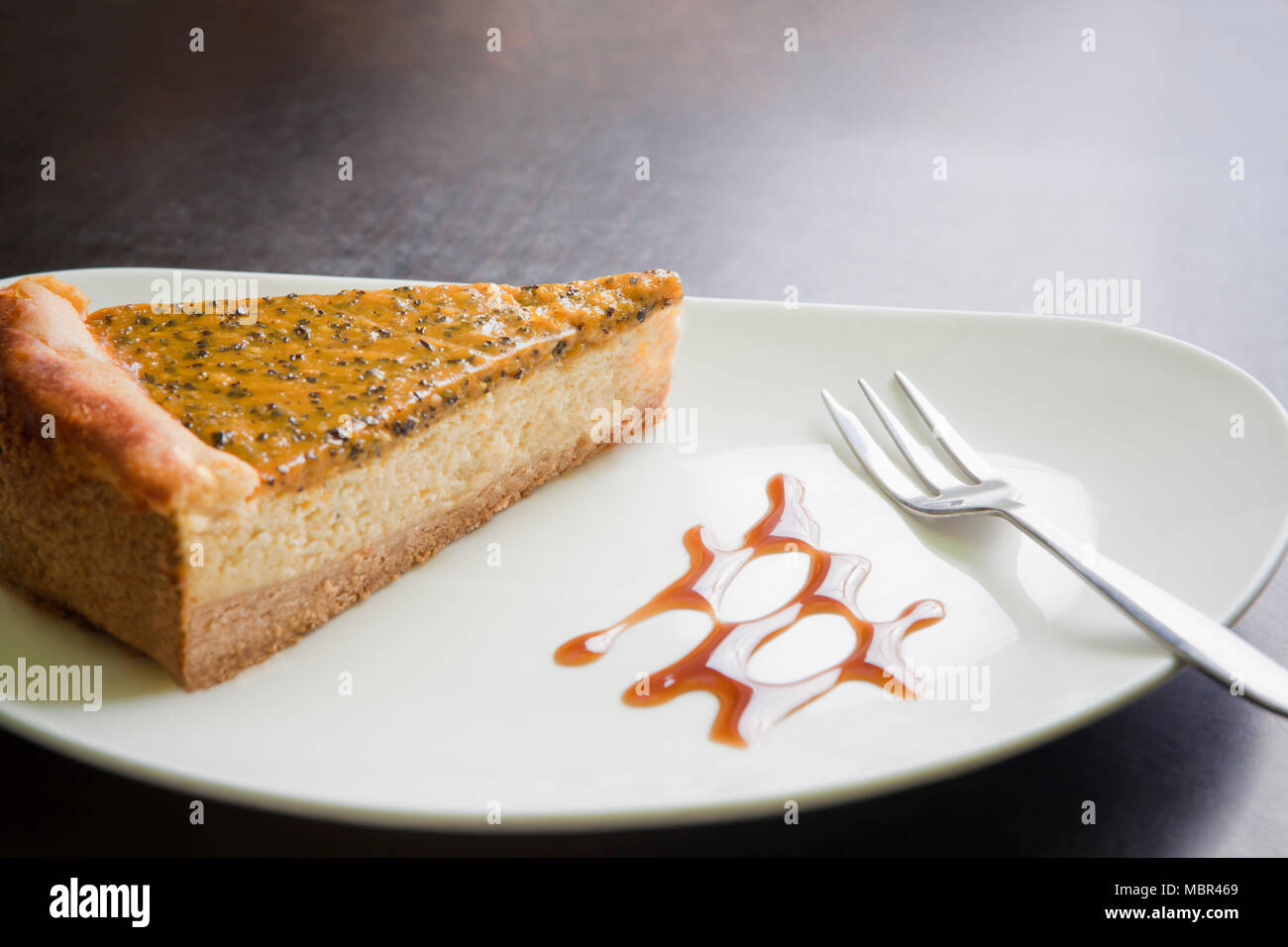 Slice of Maracuja Cheesecake on a white plate; Close up - Stock Image