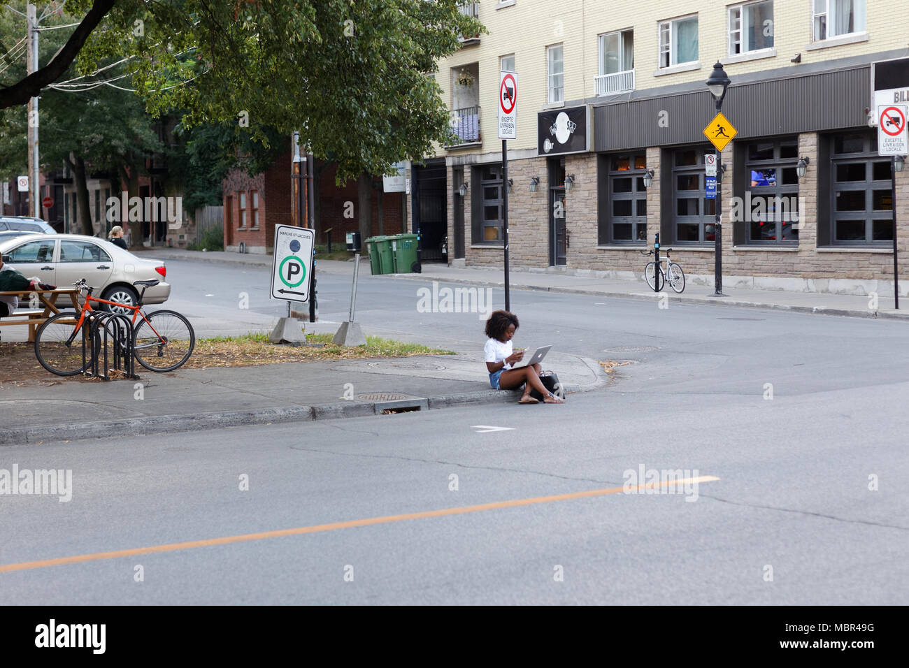 Quebec,Canada. a young black girl sitting curbside with her laptop in Montreal. - Stock Image