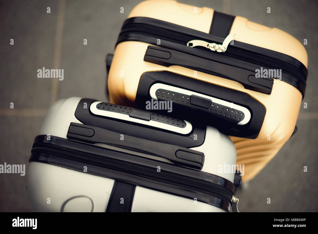 Two suitcases on grey blurred background. Summer vacation and travel concept. Traveler suitcase with copy space - Stock Image
