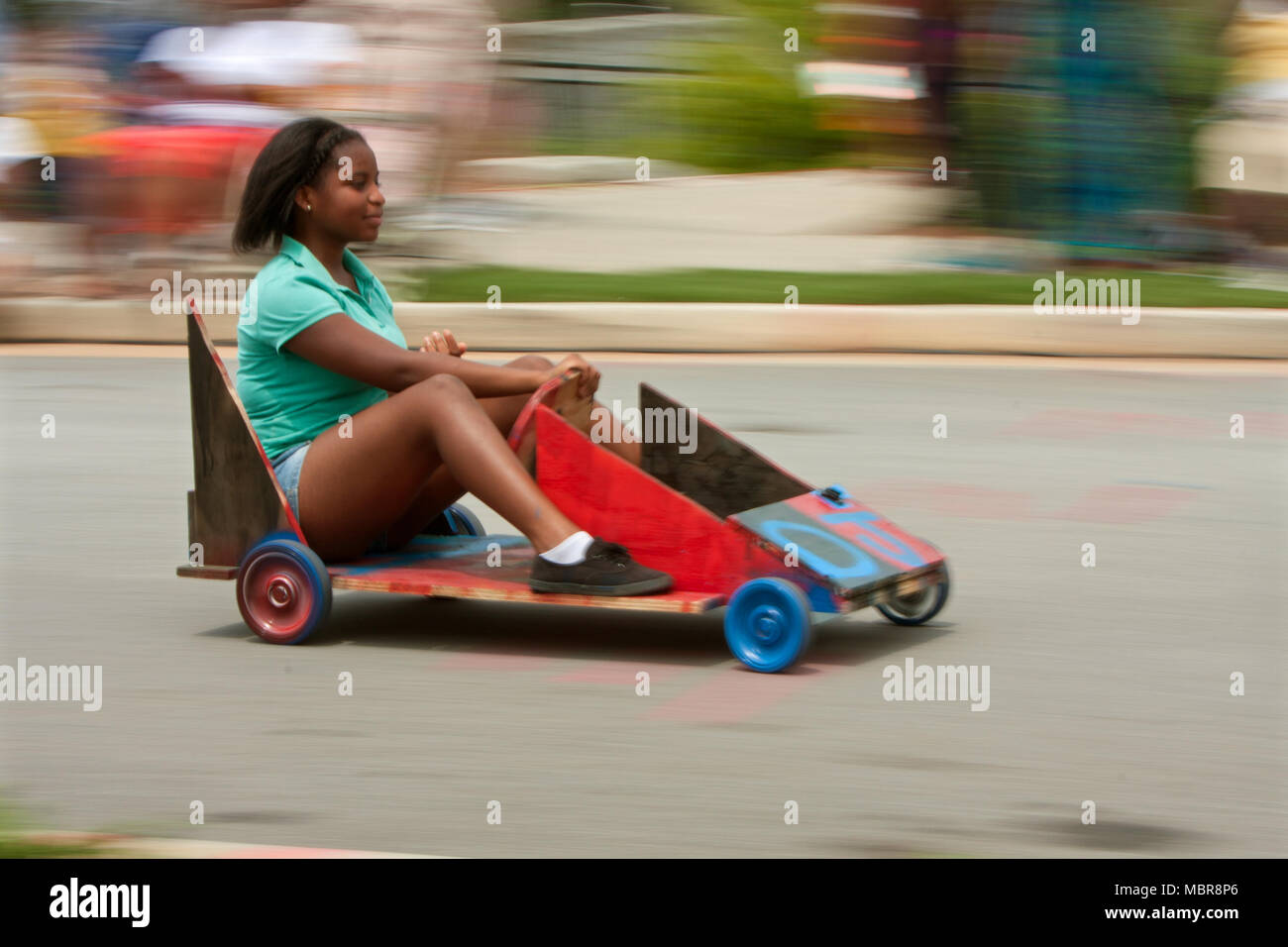 Motion blur of a teen girl steering a homemade car down a hilly street in the Cool Dads Rock Soap Box Derby on August 3, 2013 in Atlanta, GA. - Stock Image