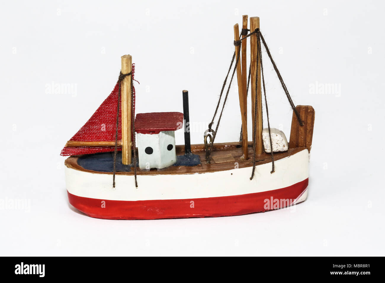 A model fishing boat made of wood, string and a small piece of cloth for the sail. It has been handmade in a traditional design. - Stock Image