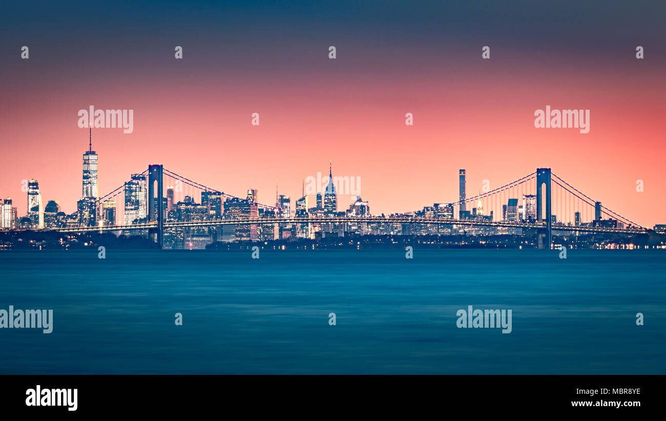 Verrazano Narrows Bridge gates the access to Upper New York Bay. Manhattan skyline rises behind the bridge. - Stock Image