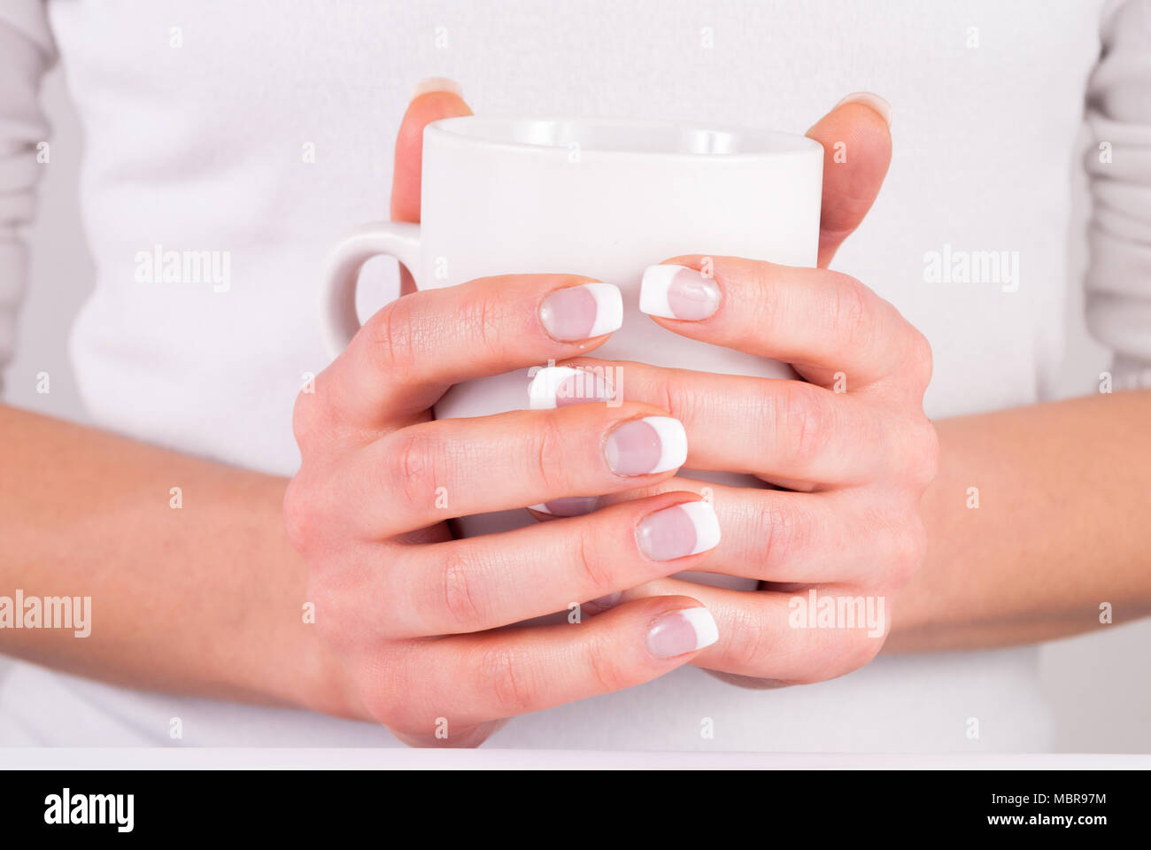 Woman hands with french nails manicure holding cup of coffee. Close ...
