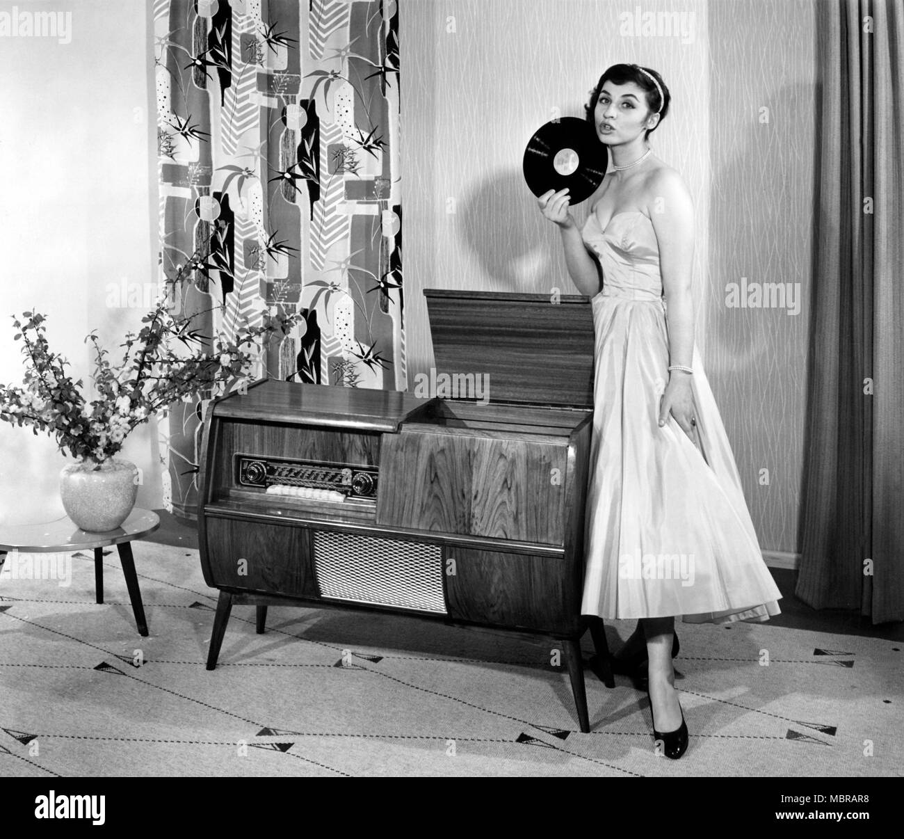 Woman in front of a record player in the living room, 1950s, Germany - Stock Image