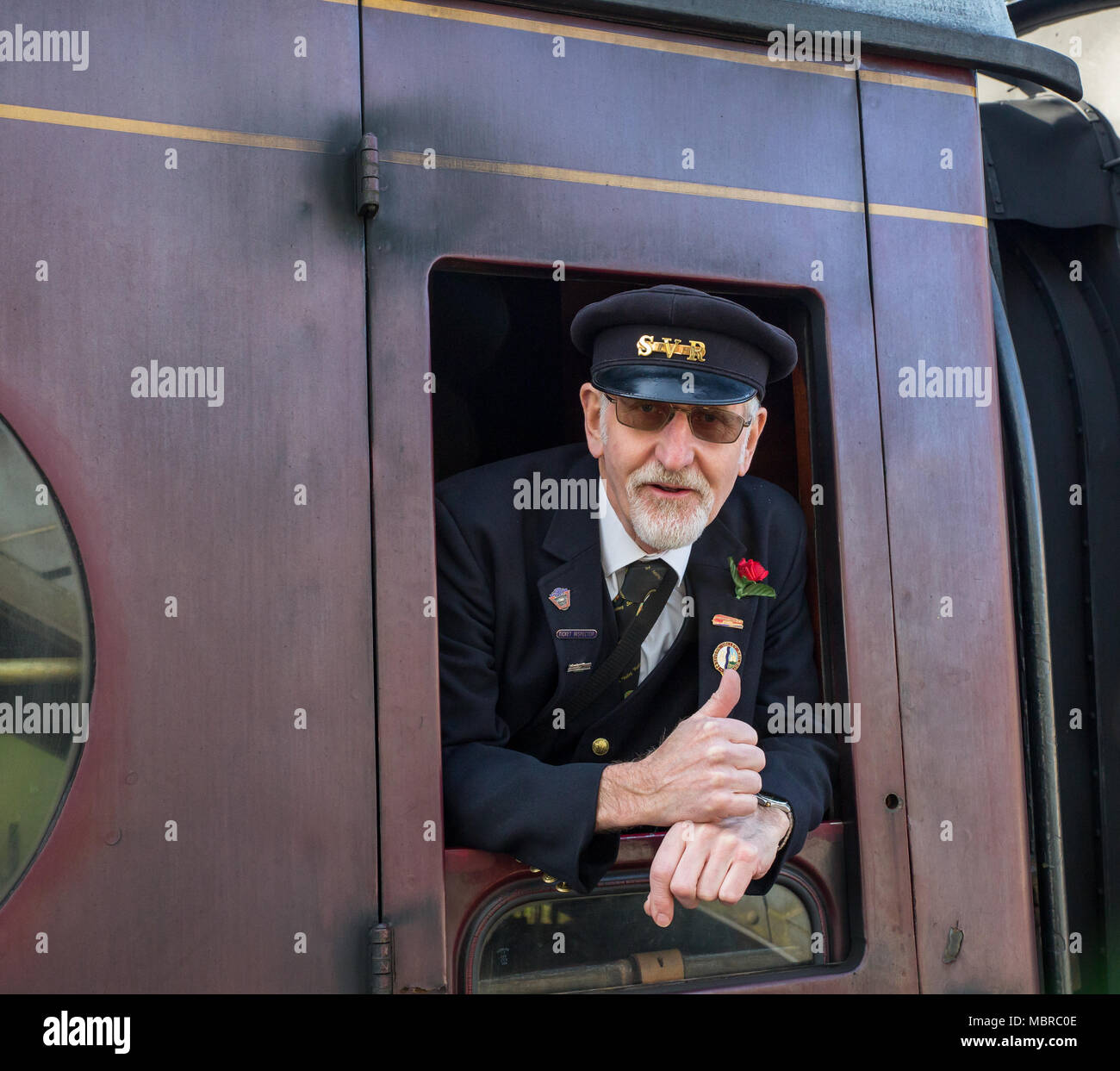 Close up of jolly SVR guard, in official cap, captured as he leans out of passing carriage giving a happy 'thumbs up' to poised platform photographer. - Stock Image