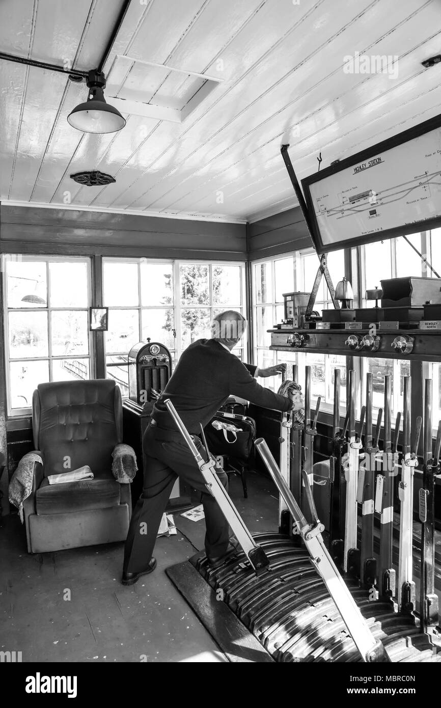Black & white action shot of lone signalman operating equipment, pulling levers, inside the signal box at Severn Valley Railway's Highley Station. - Stock Image
