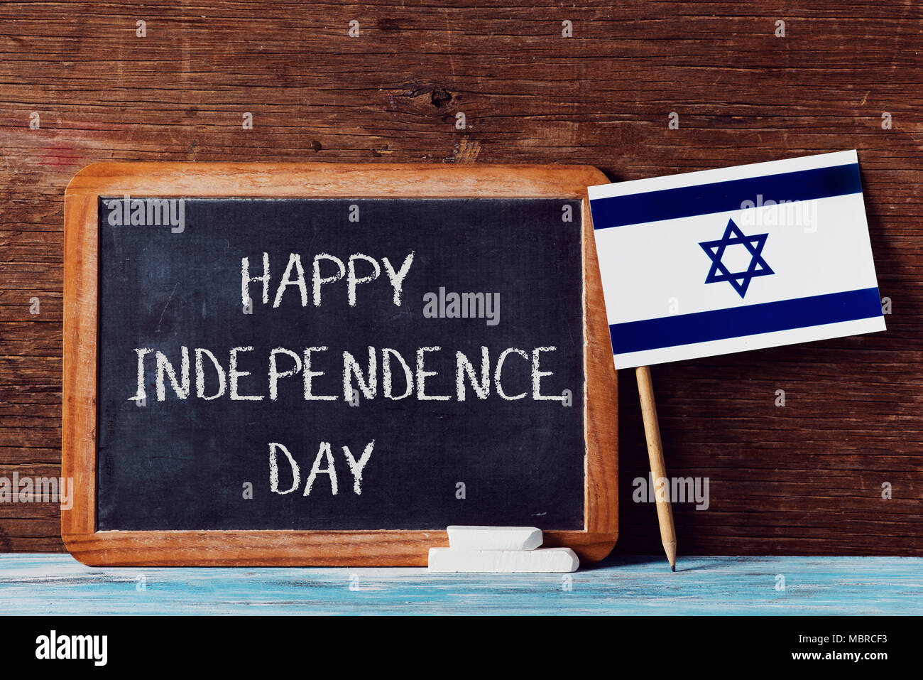 a wooden-framed chalkboard with the text happy independence day written in it, some pieces of chalk and an israeli flag on a rustic wooden surface Stock Photo