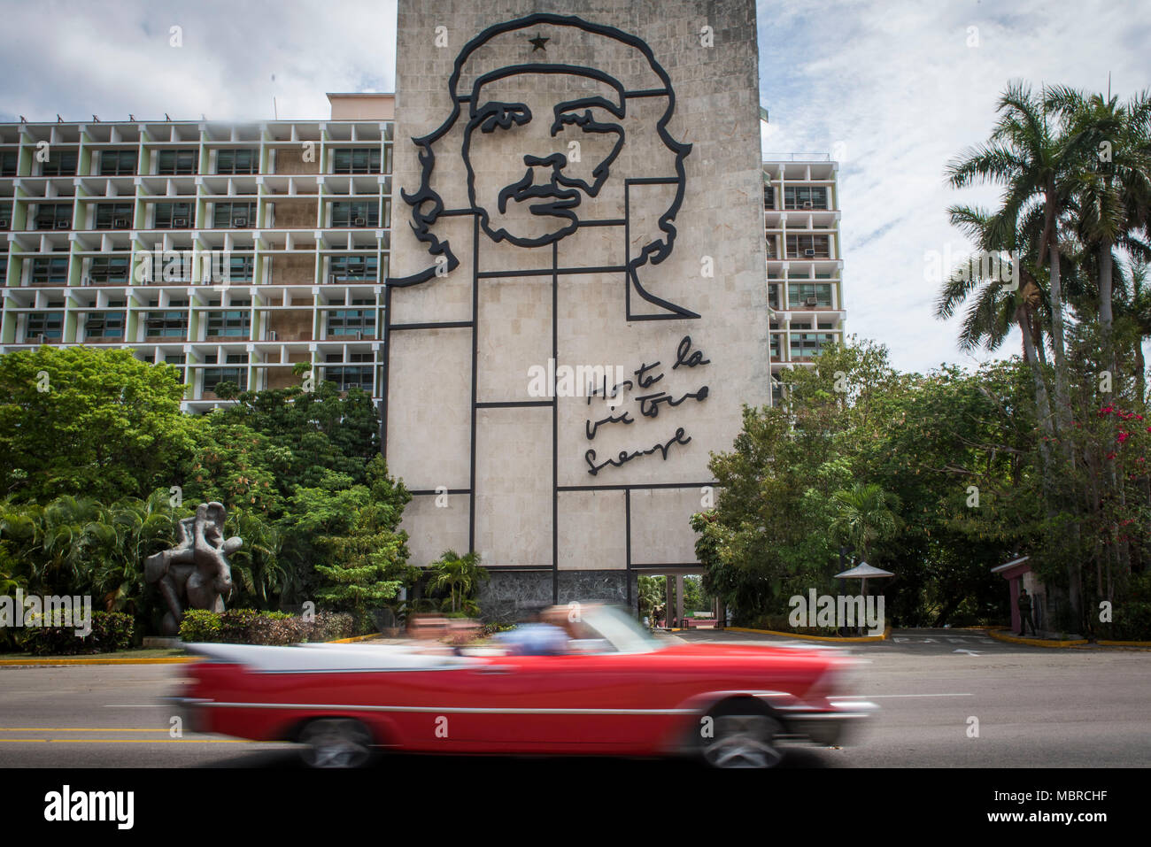 Classic American car drives past a building with a Che Guevara mural on the side in Revolution Square, Havana, Cuba. - Stock Image