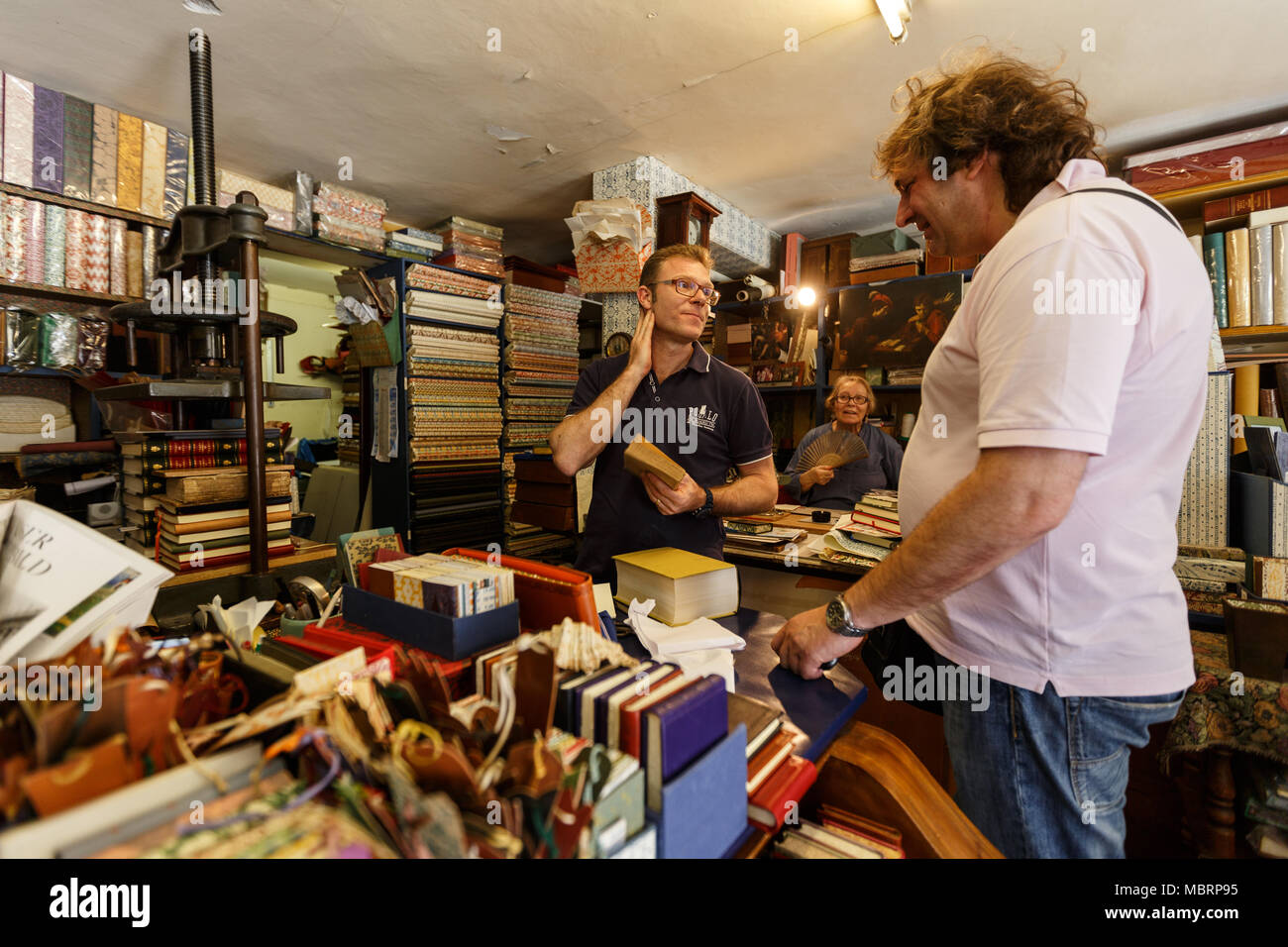 The owner and visitor are kindly discussing the restoration of books. Venice - Stock Image