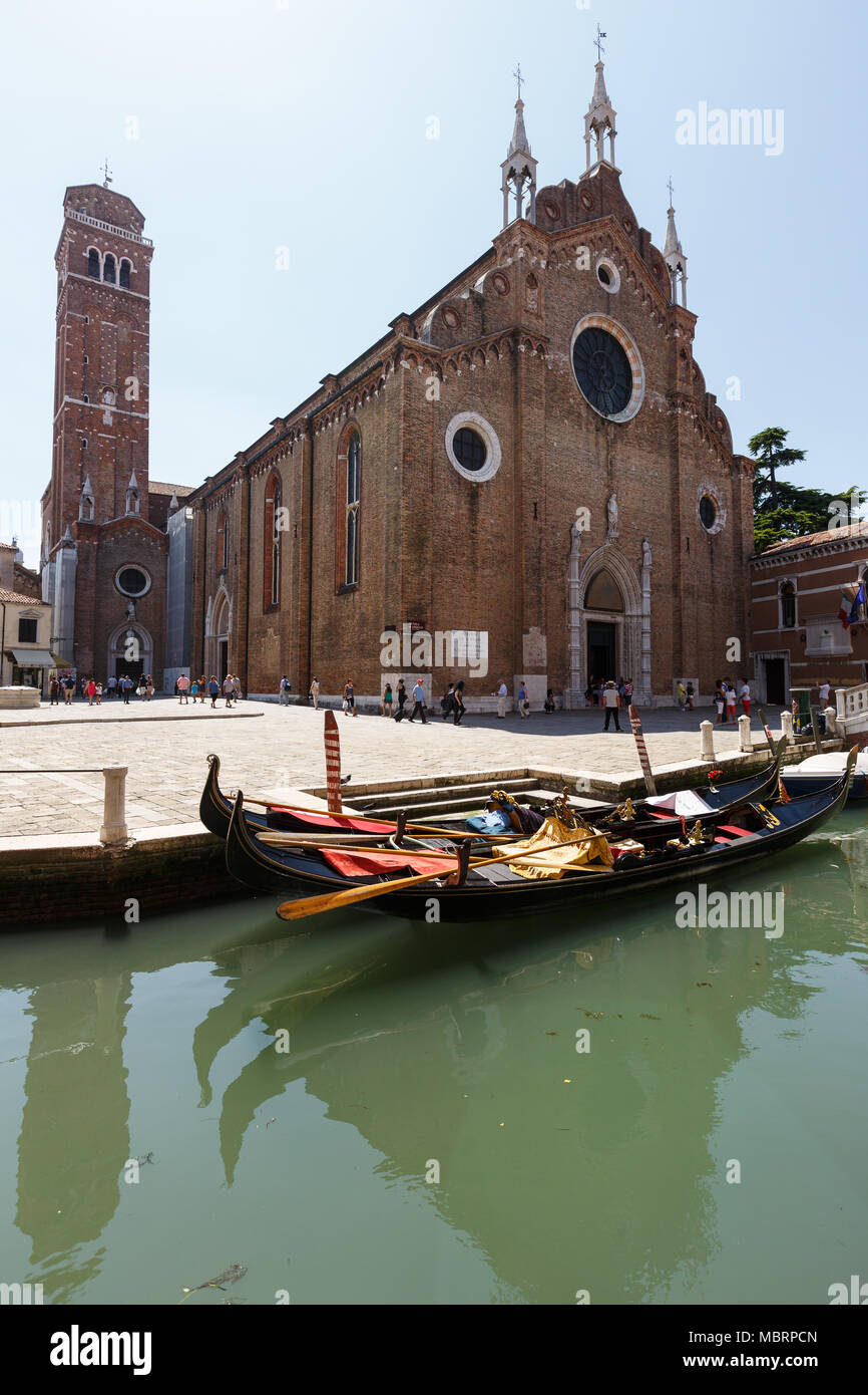 Channel with gondolas, Basilica of Santa Maria Gloriosa dei Frari on background - Stock Image