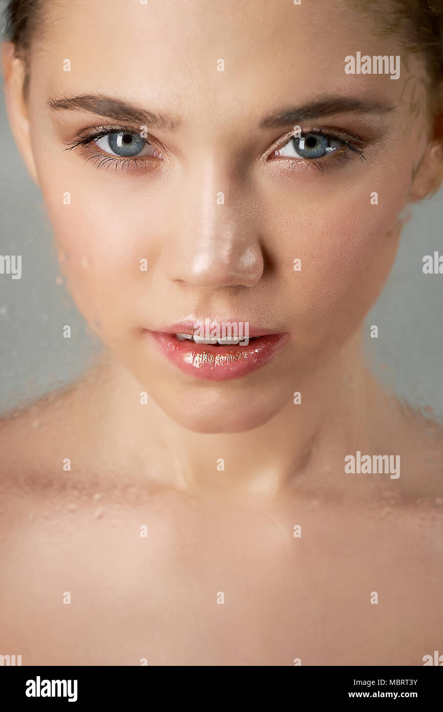 Portrait of young beautiful girl in Studio, with professional makeup.Beauty shooting. In the face of a transparent glass with water droplets. Hydration of the skin - Stock Image