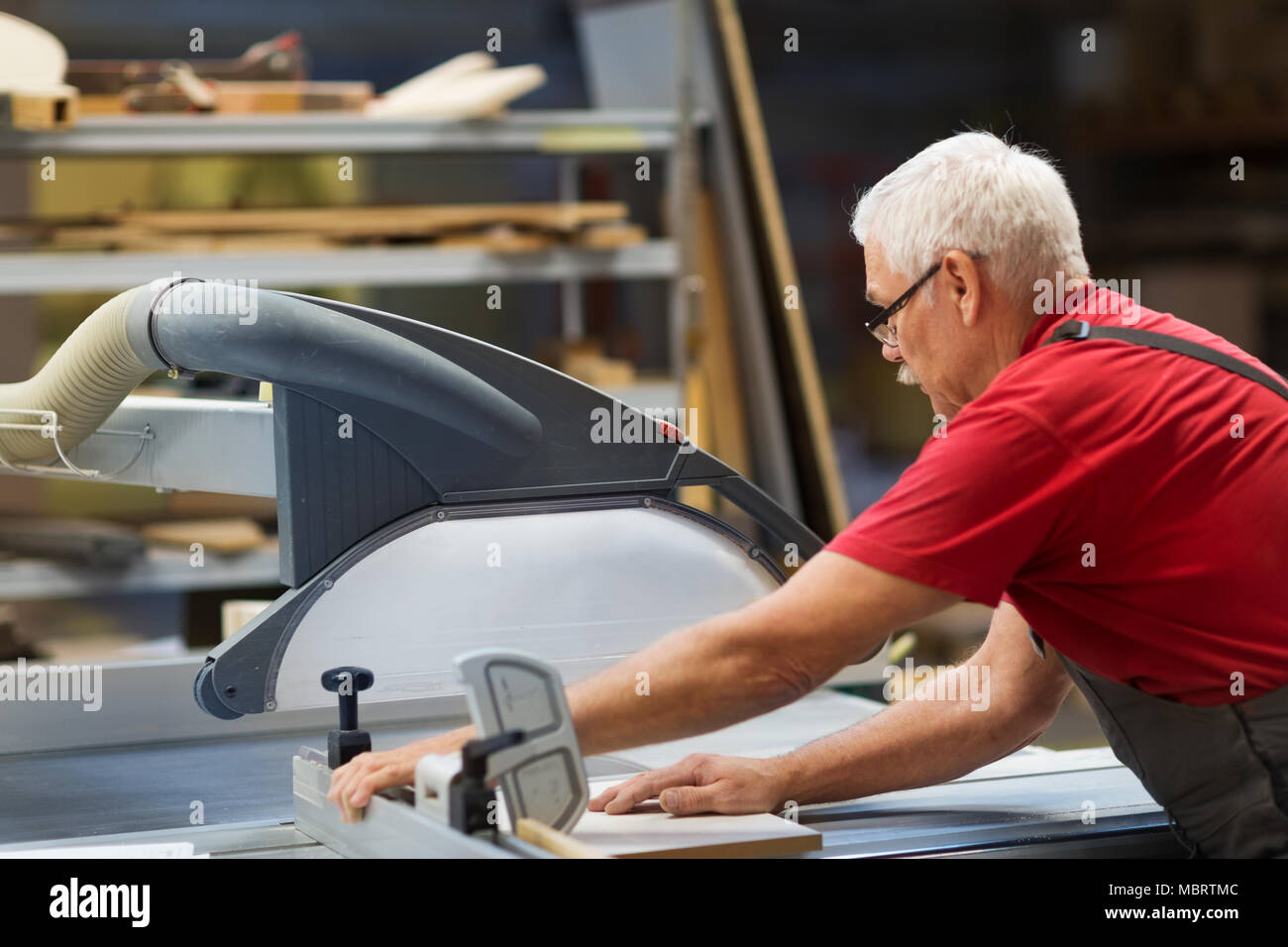 carpenter with panel saw and fibreboard at factory - Stock Image
