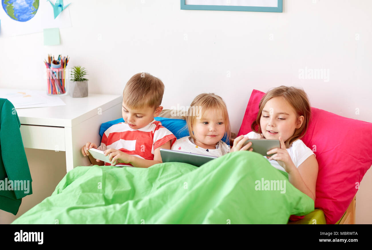 kids with tablet pc and smartphones in bed at home - Stock Image