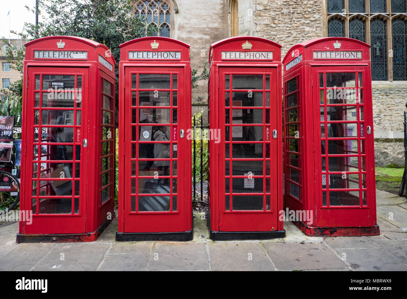 Four red telephone boxes in St. Mary's Passage in the university city of Cambridge England UK - Stock Image