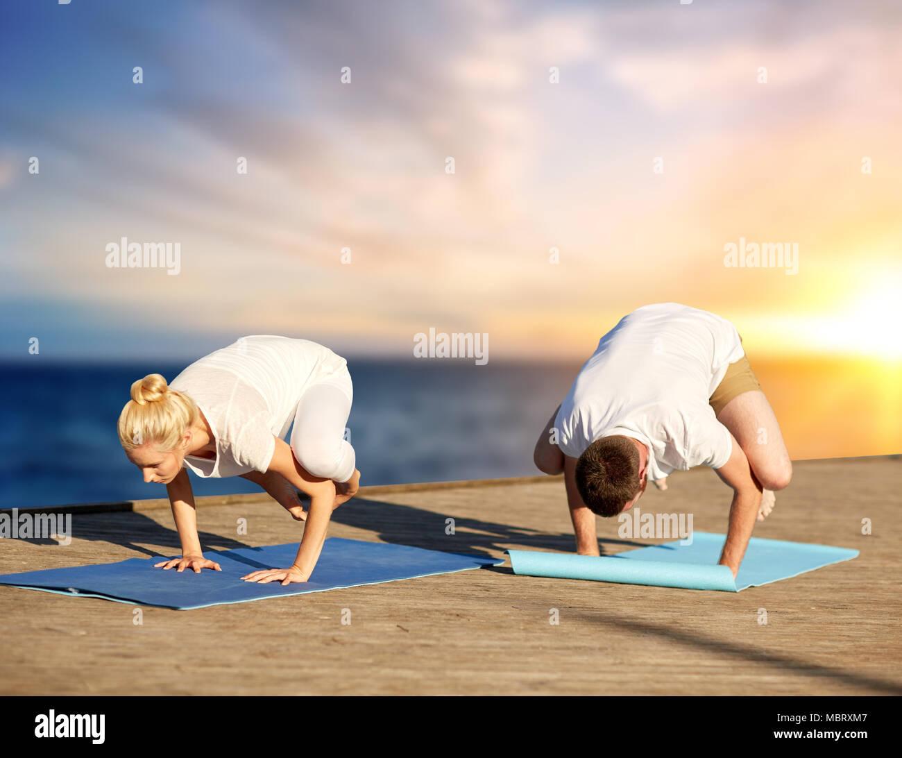 Couple Doing Yoga Crow Pose Outdoors