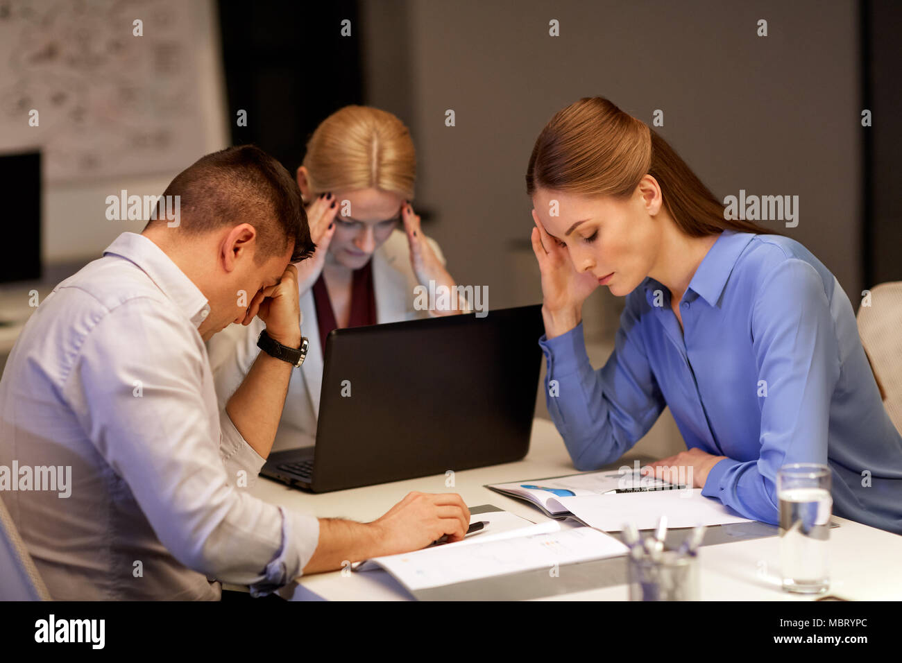 business team with laptop working at night office - Stock Image