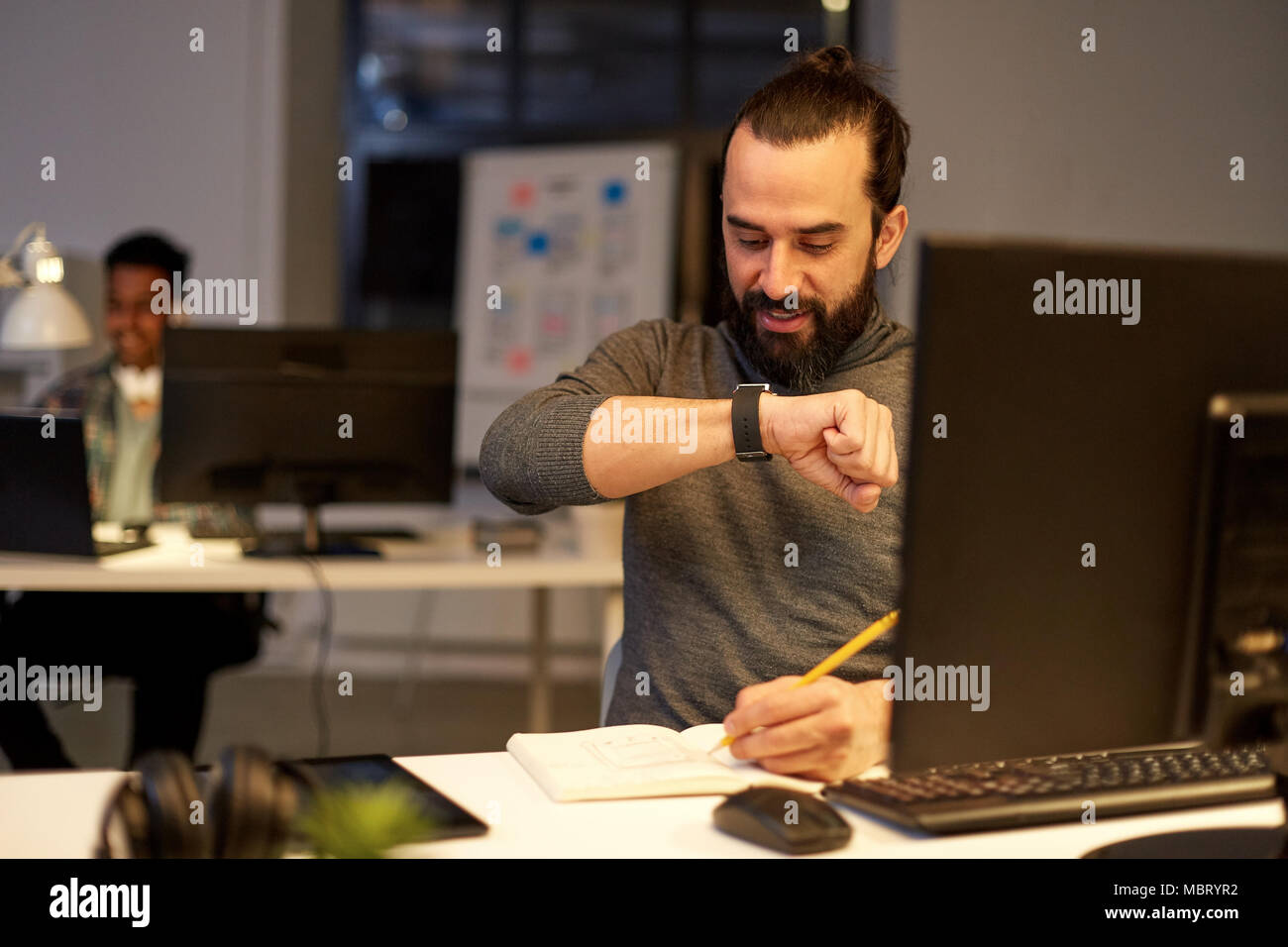 man with smartwatch using voice recorder at office - Stock Image