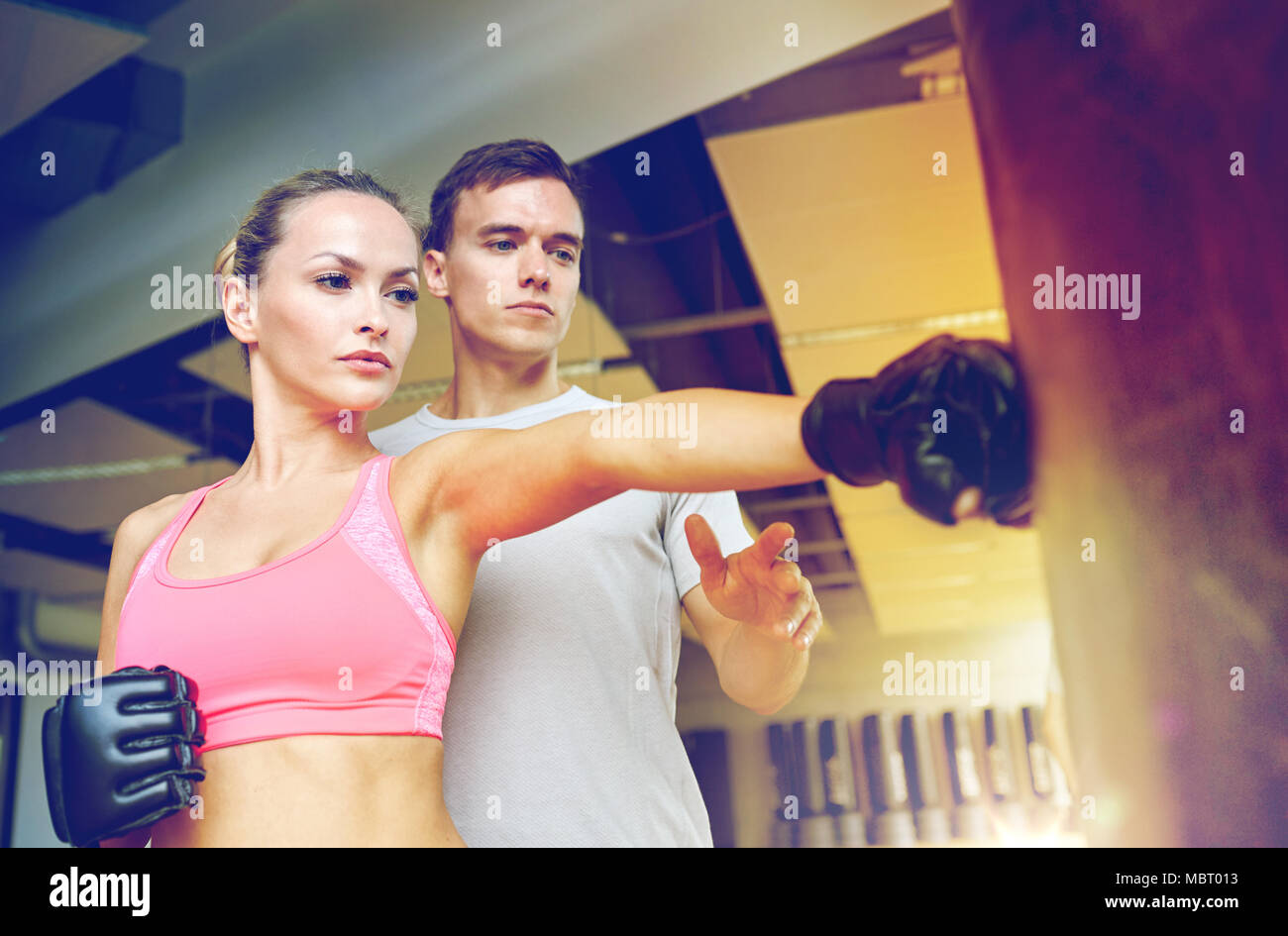 woman with personal trainer boxing in gym - Stock Image