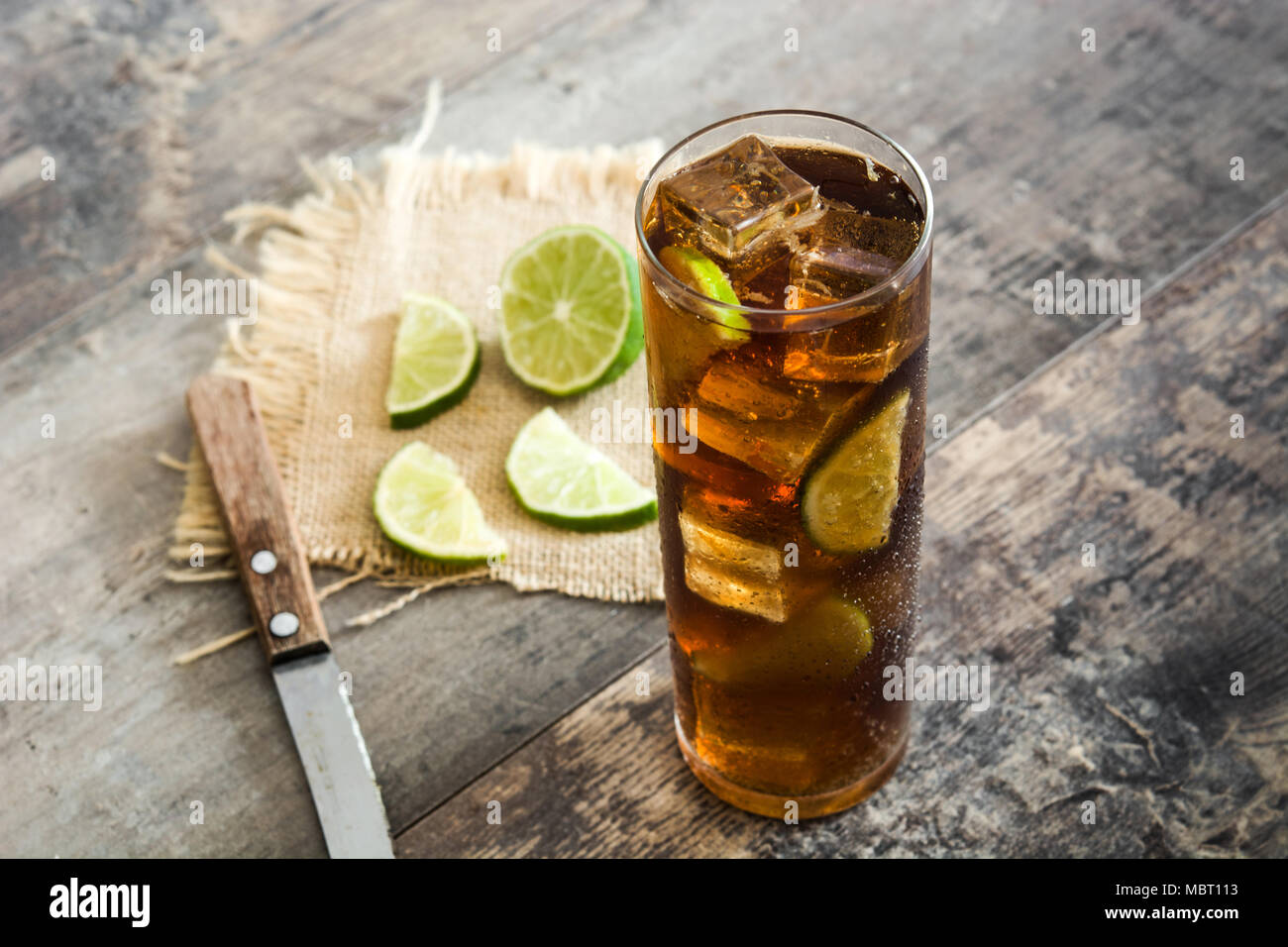 Cuba libre. Cocktail with rum, lime and ice on wooden table - Stock Image