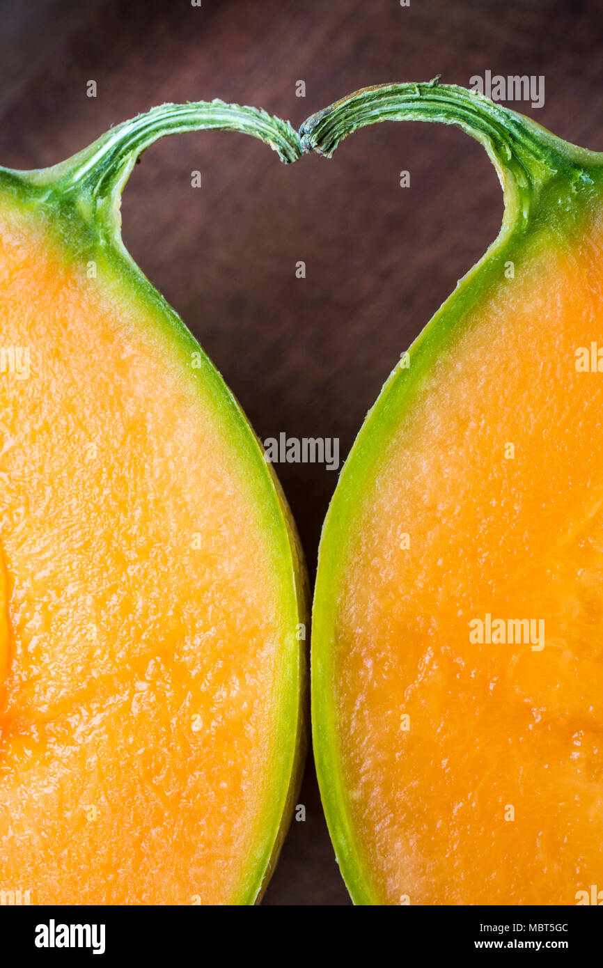 The space between two halves of a melon and its stalk forms a heart shape. - Stock Image