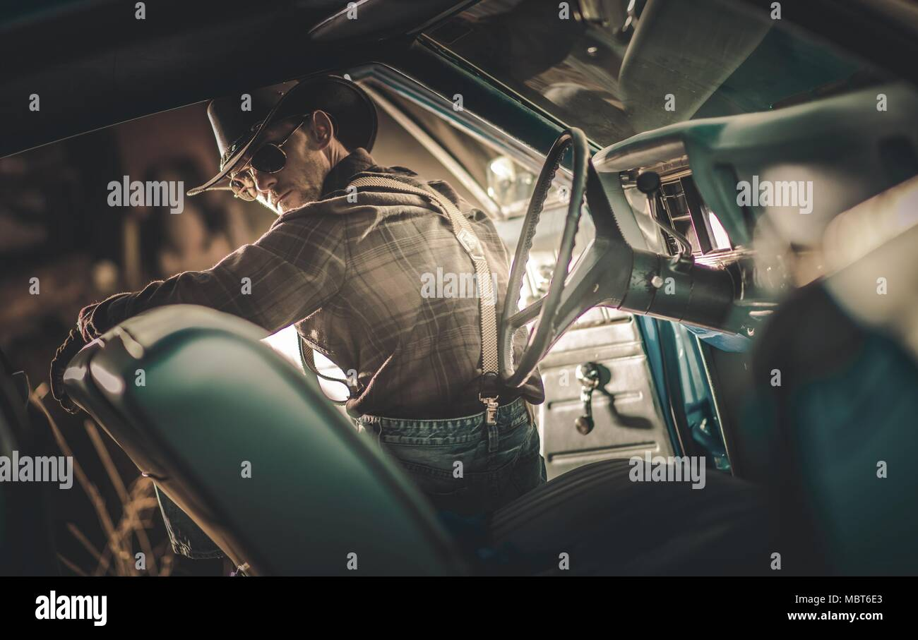 American Caucasian Cowboy Driver in His 30s Wearing Western Clothes and Sunglasses Seating Inside American Classic Muscle Car. American Countryside Th - Stock Image
