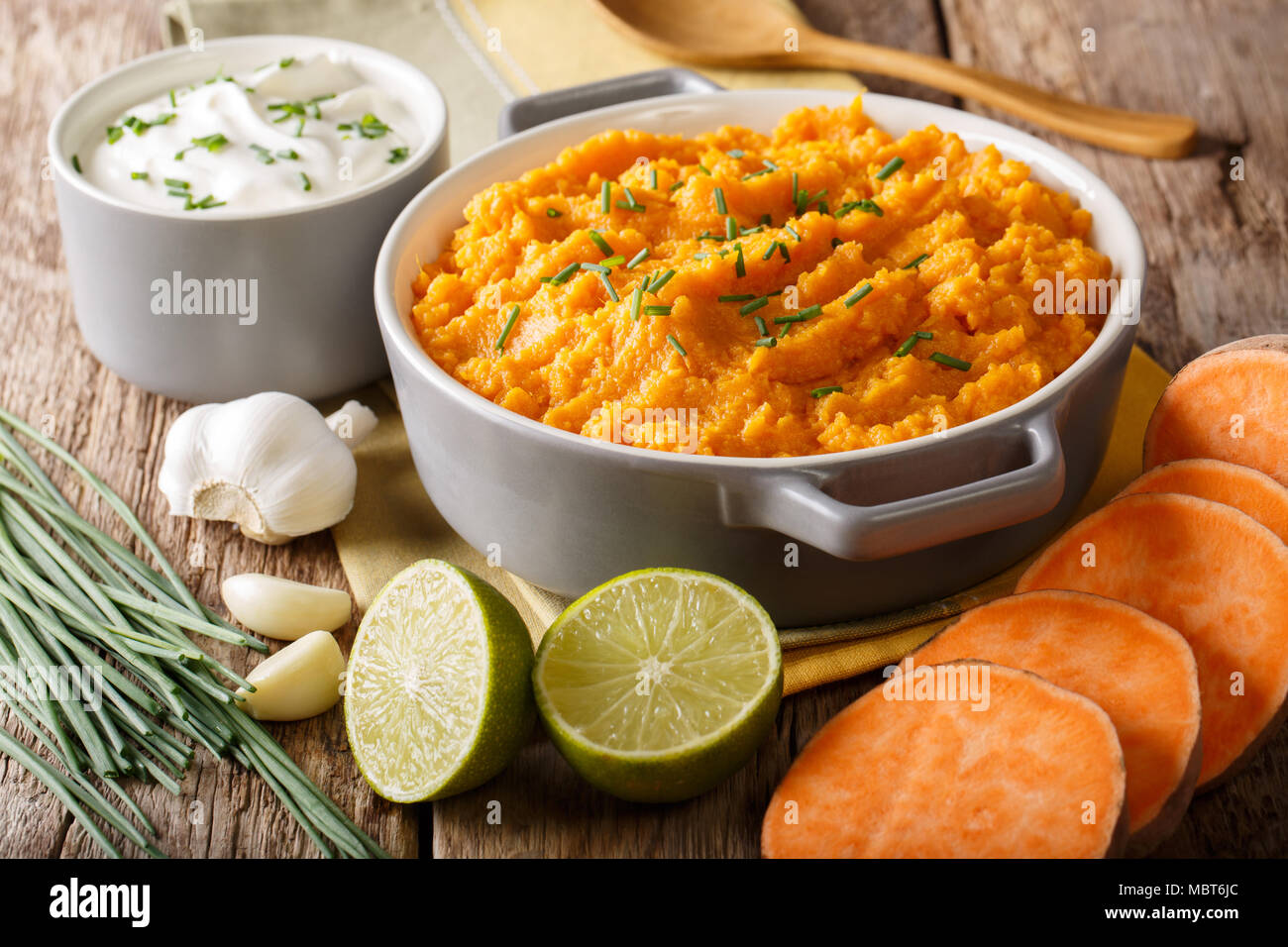 Freshly prepared mashed sweet potatoes with herbs, garlic and lime close up in a pot on the table. horizontal - Stock Image