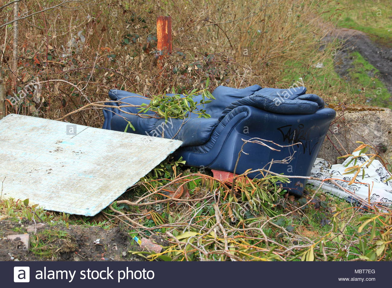A sofa dumped on recreational ground along the canal in Staybridge Cheshire Tameside England - Stock Image