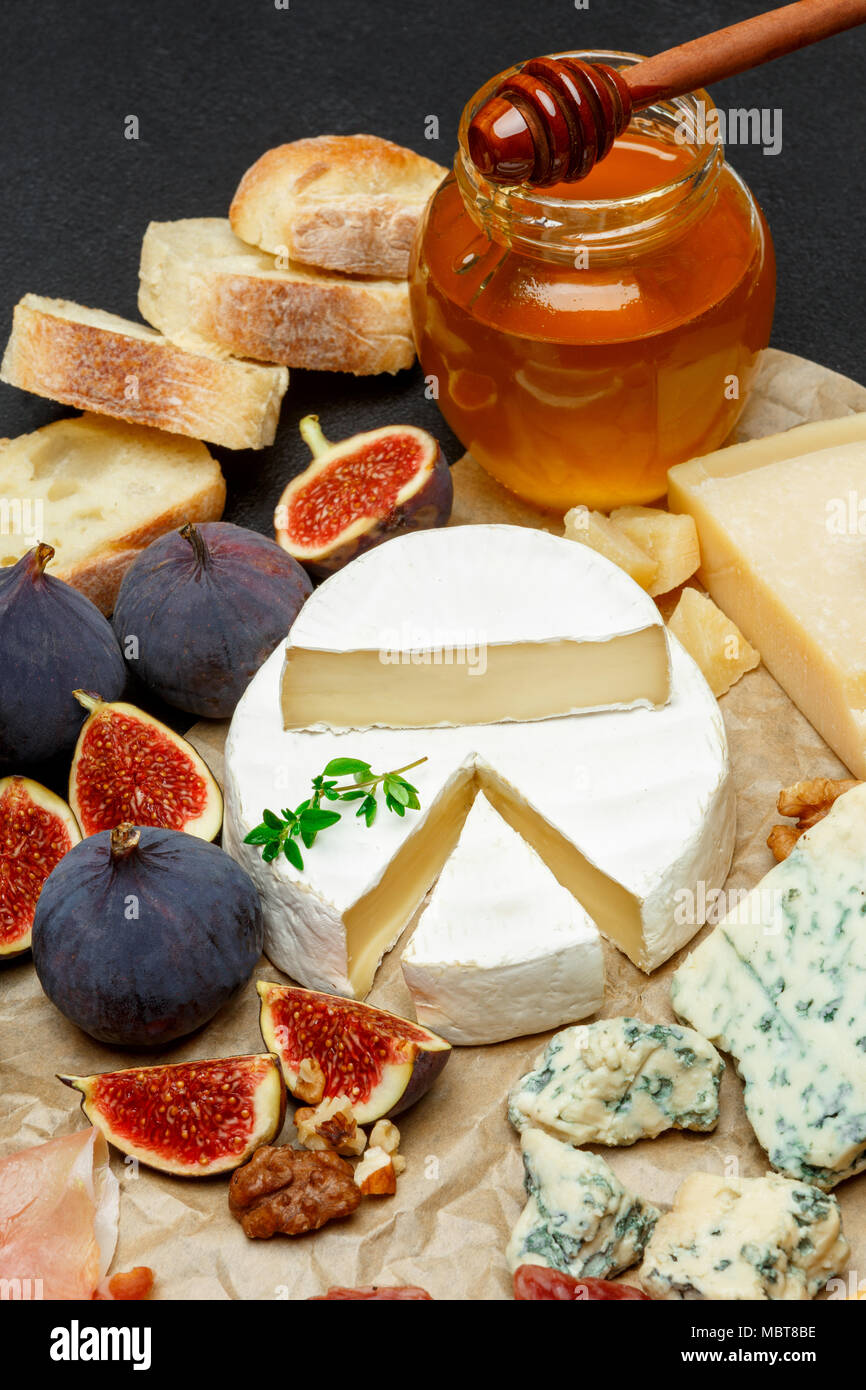 Brie cheese on a wooden Board with fresh figs and honey - Stock Image