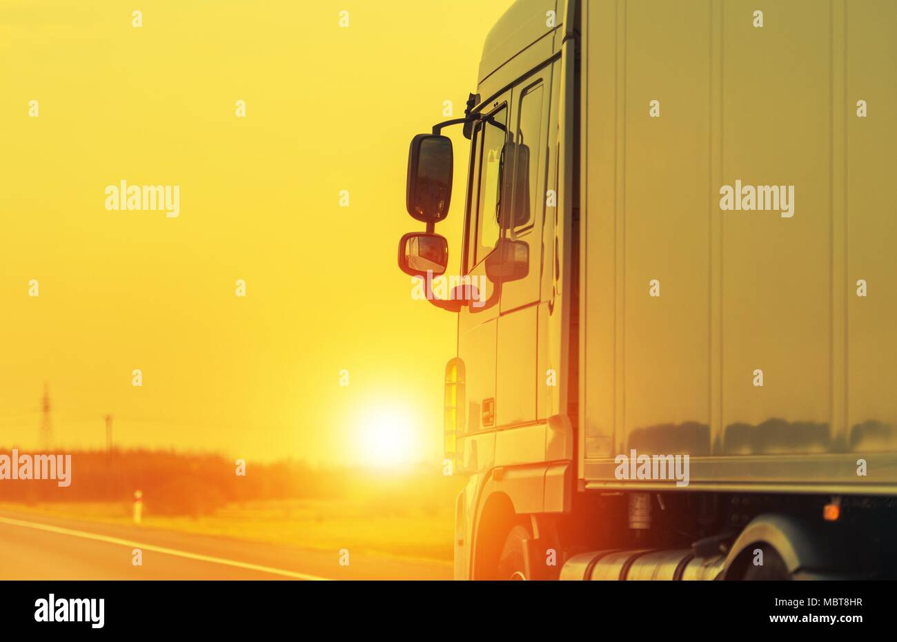 Road Shipping by Semi Truck. Heavy Load Long Haul Euro Transportation Theme. Sunset on the Highway. - Stock Image
