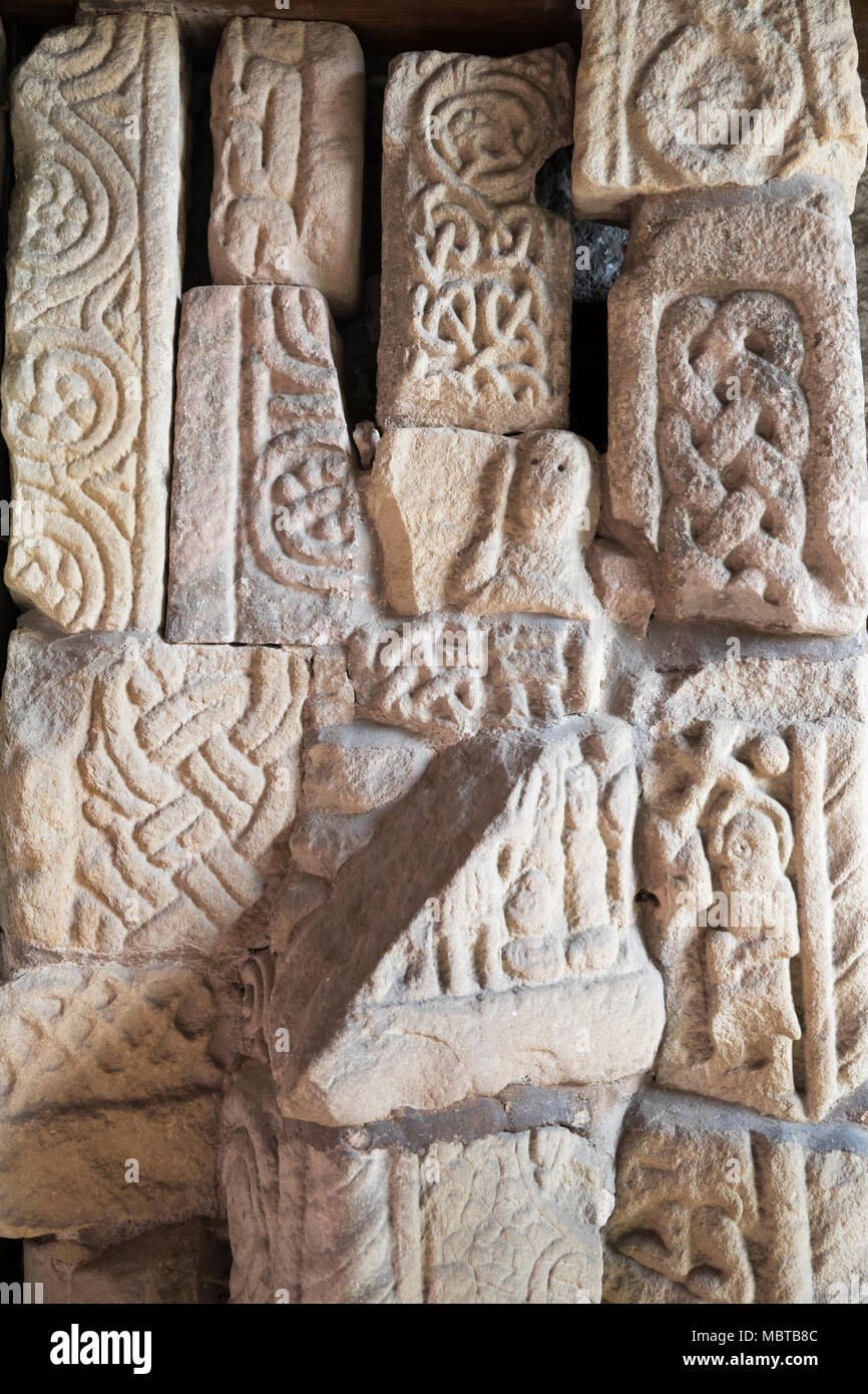 Carved Anglo-Saxon and Norman stone fragments in the porch of All Saints Church, Bakewell, Derbyshire, England, United Kingdom, Europe - Stock Image