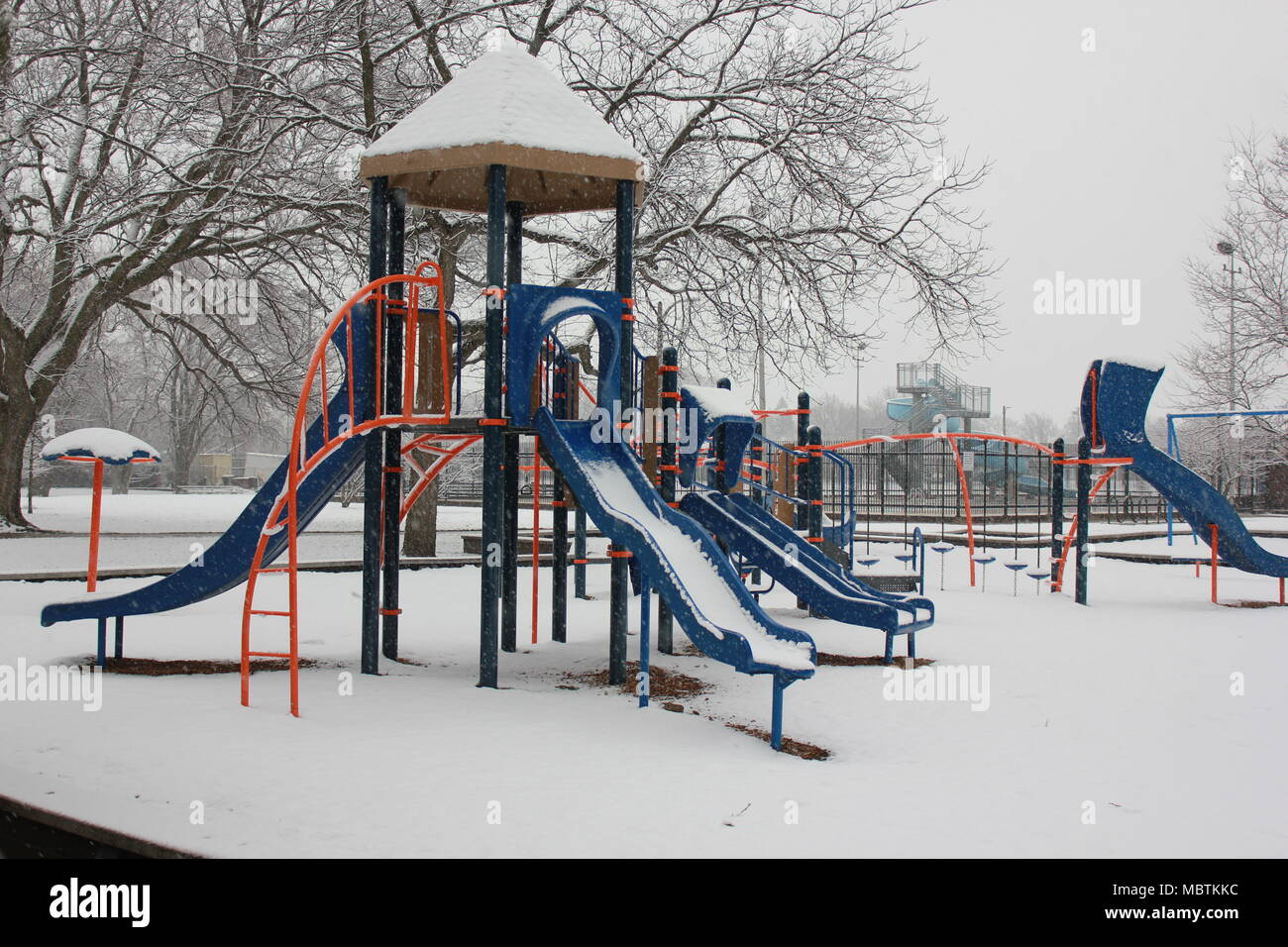 Chicago's Norwood Park's empty playground just after snowfall in a cloudy day. - Stock Image