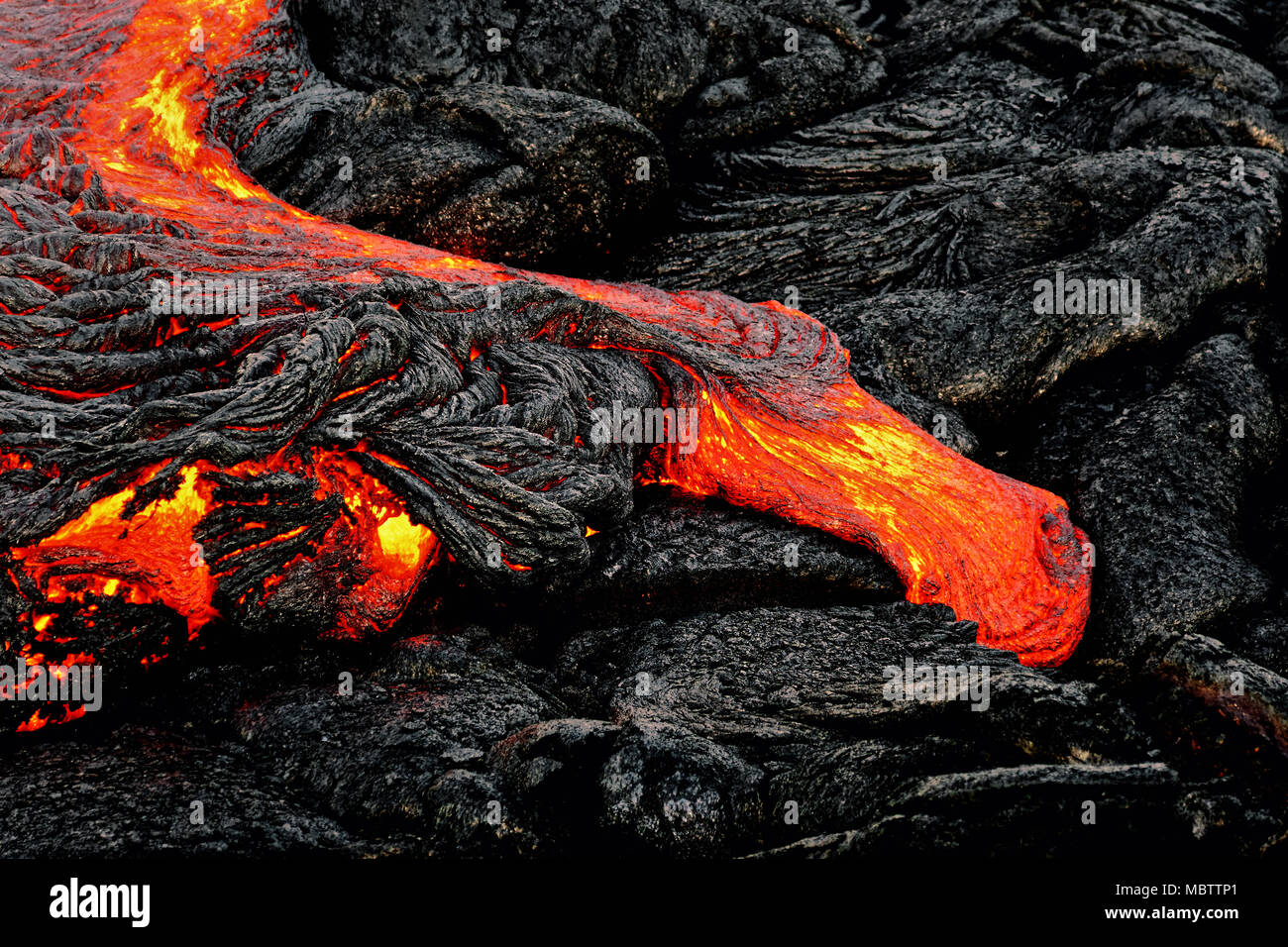 Hot magma escapes from an earth column as part of an active lava flow, the glowing lava slowly cools and freezes - Location: Hawaii, Big Island, volca - Stock Image