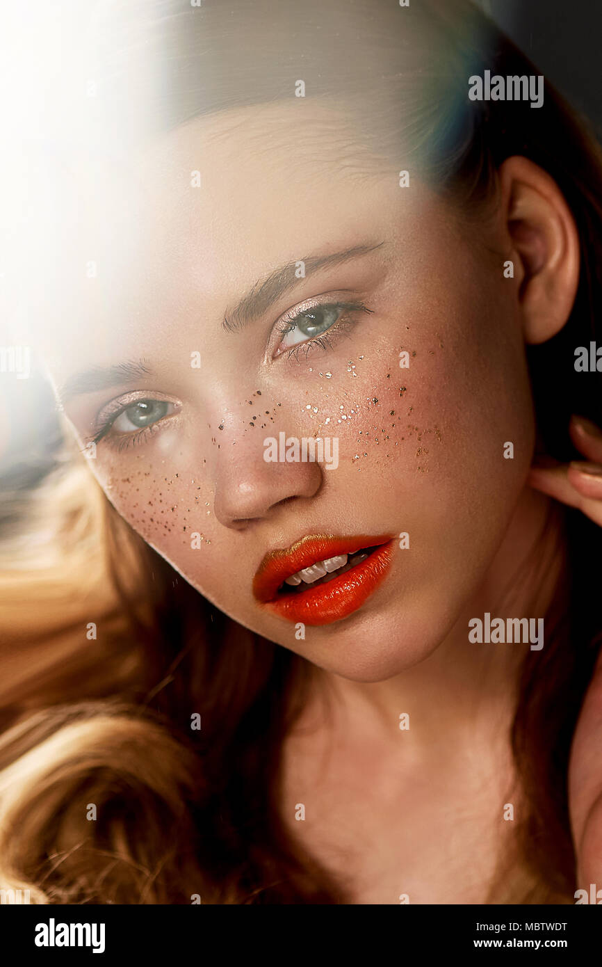 Portrait of young beautiful girl in Studio, with professional makeup.Beauty shooting.The warm Golden glare. Gold sequins freckles. Feeling the warmth of the sun on the skin. - Stock Image
