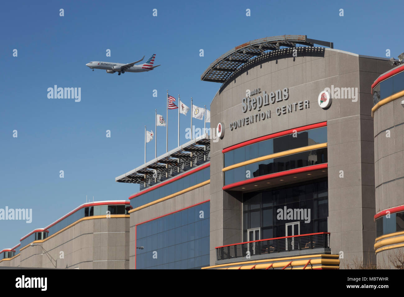 Rosemont, Illinois - An American Airlines jet about to land at O'Hare Airport flies over the Donald E. Stephens Convention Center. - Stock Image