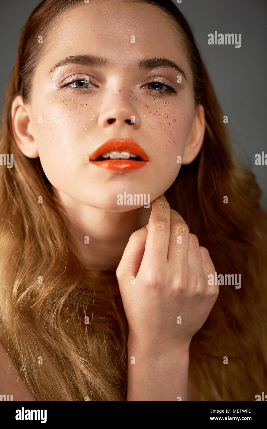 Portrait of young beautiful girl in Studio, with professional makeup.Beauty shooting. Beauty portrait of a beautiful girl with clean skin.Bright orange lips Golden freckles - Stock Image